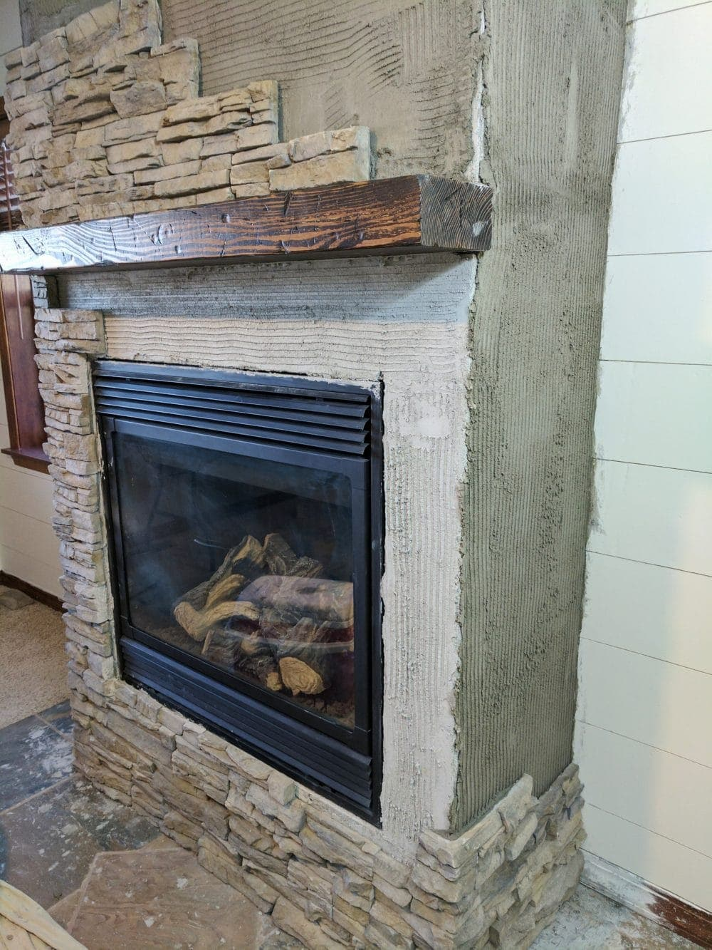 installing stone veneer on a fireplace for a remodel