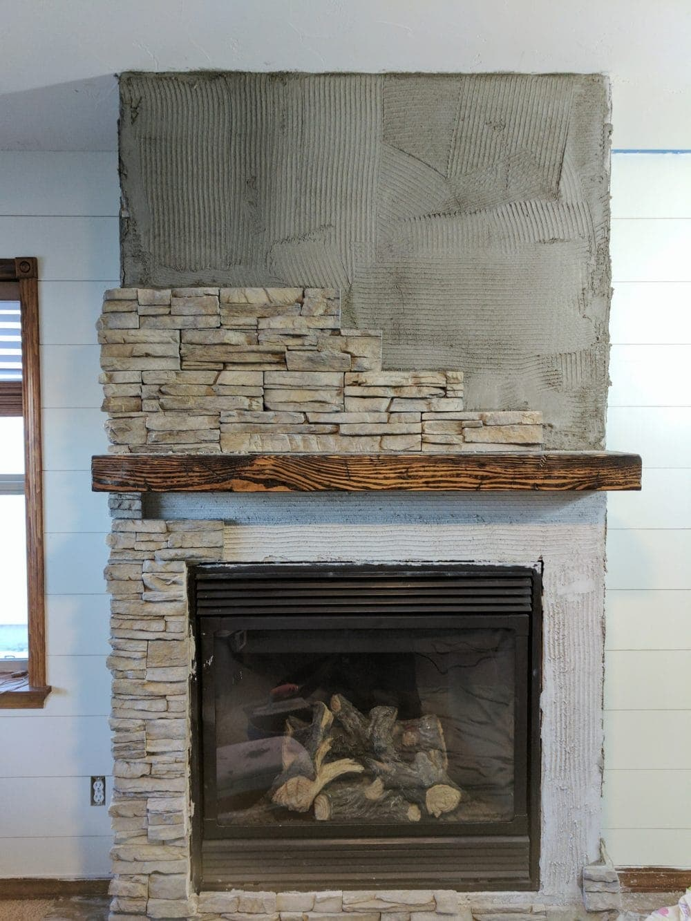 stacked stone gas fireplace with the stone veneer half installed