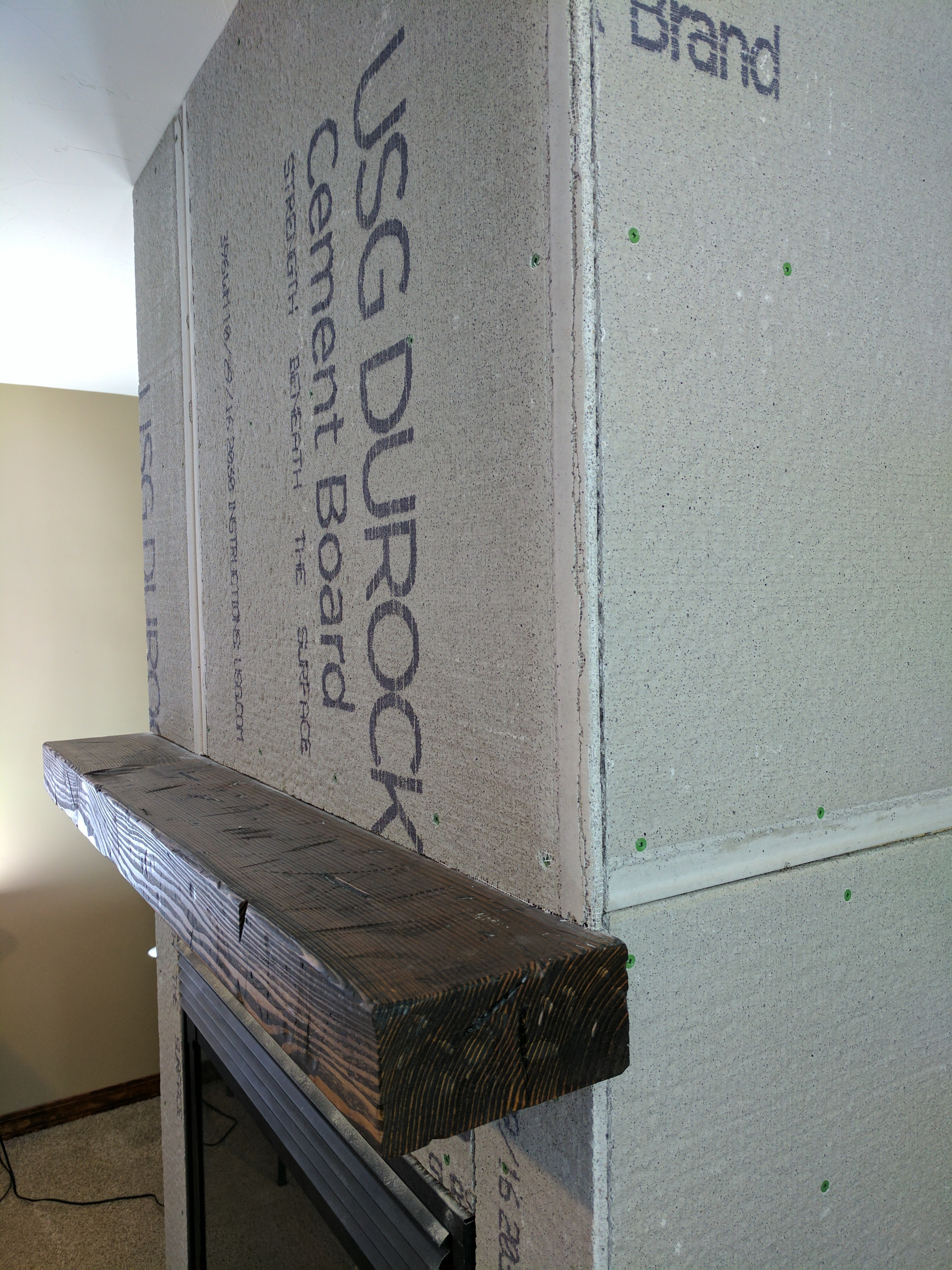 a distressed wood beam mantle hung on cement board
