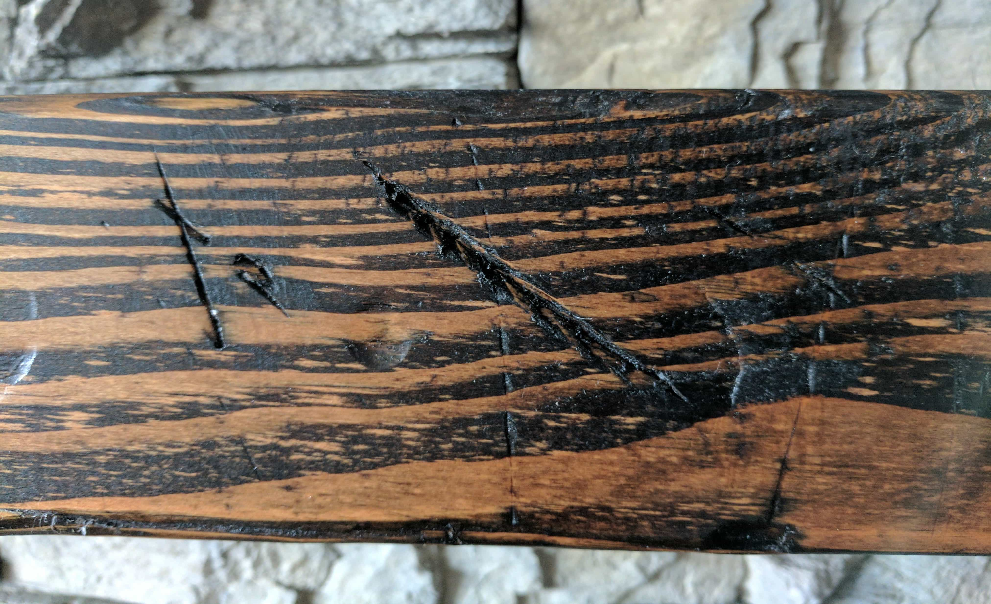 close up of a distressed wood beam mantle