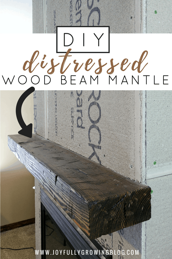 a distressed wood beam mantle hung on an unfinished fireplace
