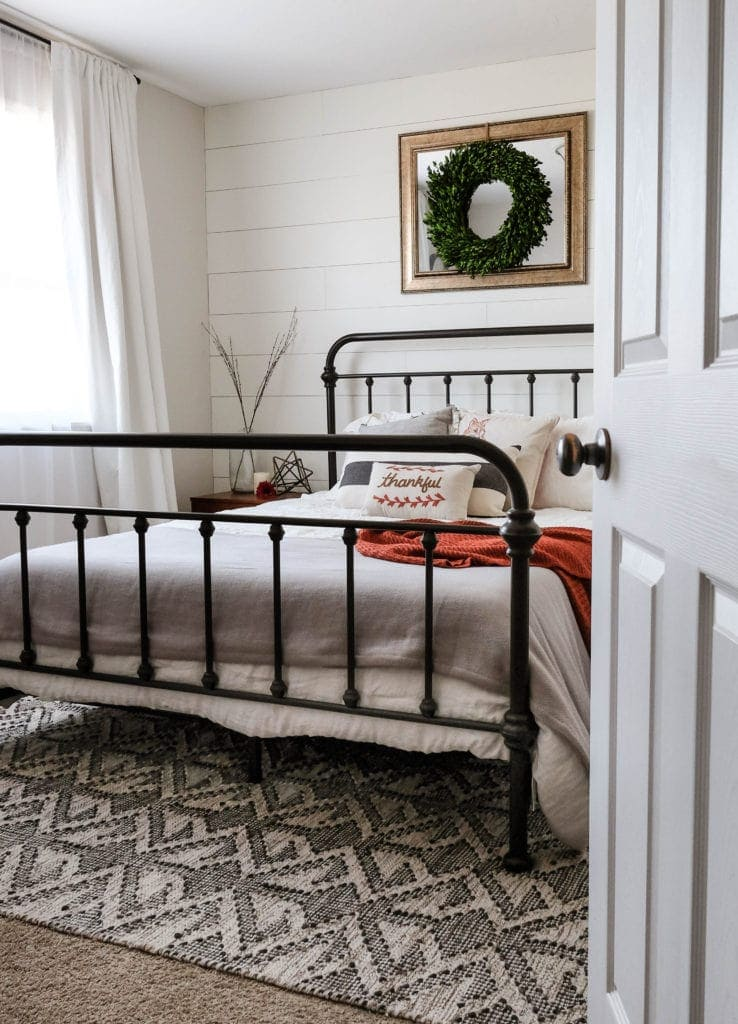 a modern farmhouse bedroom with white shiplap wall