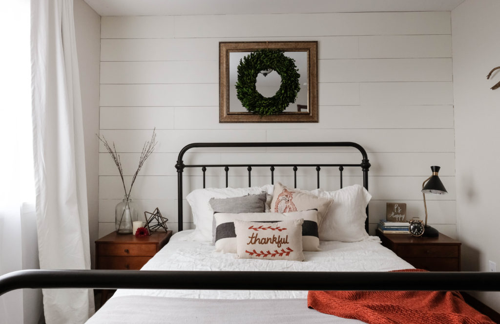 farmhouse bedroom with headboard against white shiplap accent wall