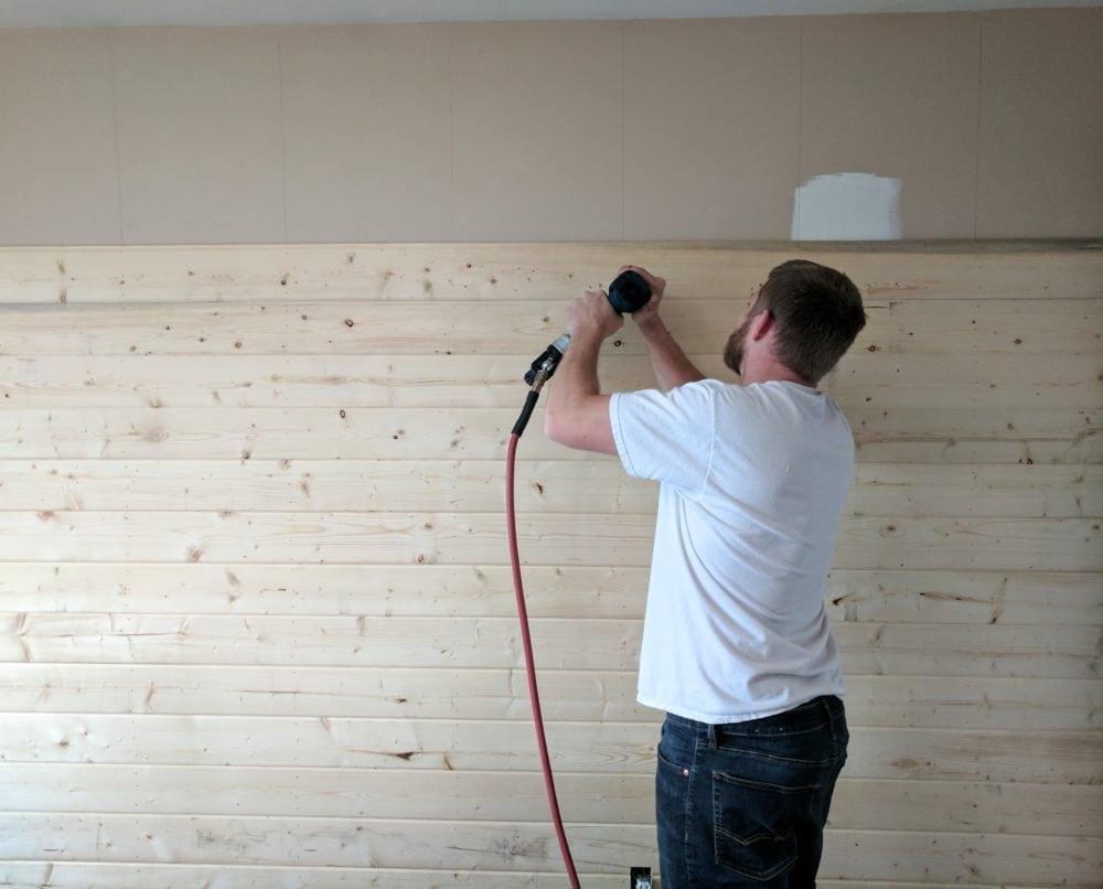A man using a nail gun on a DIY wood accent wall