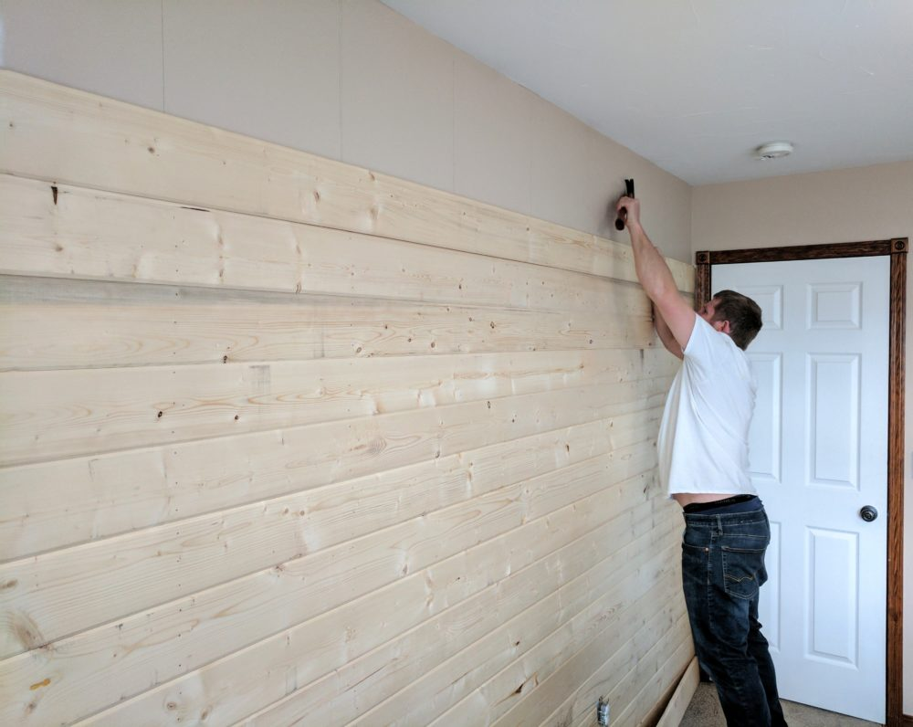 a man installing a DIY wood plank accent wall