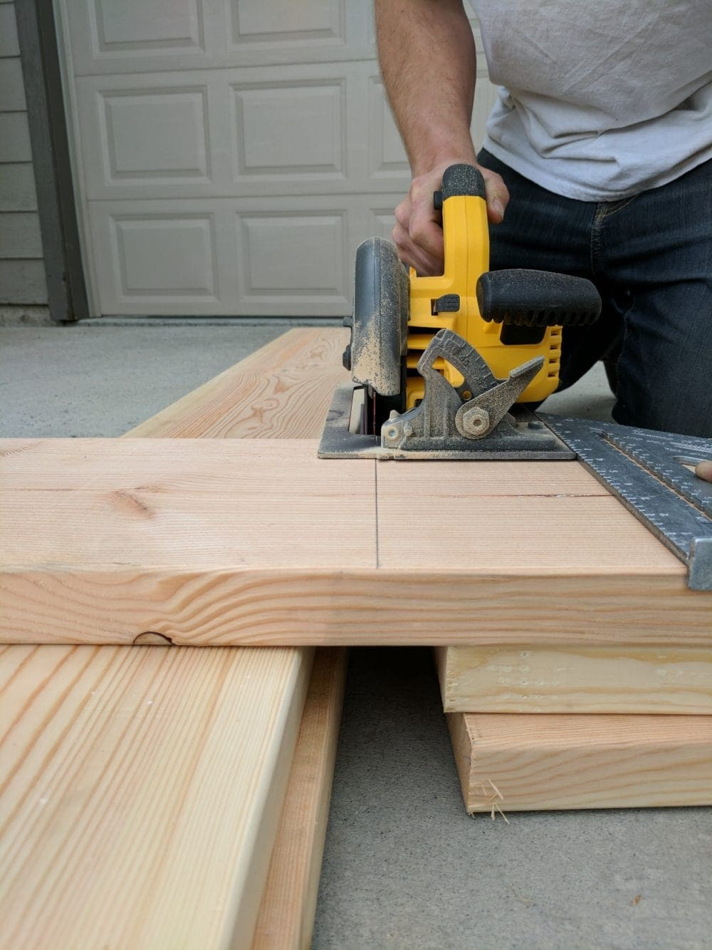 "Man Using A Dewalt circular saw to cut a 2"" x 10"" board"