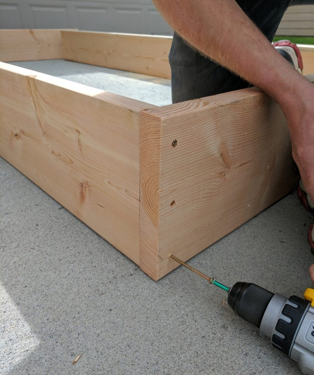 Assembling DIY Raised Garden Beds with a drill for a how to tutorial