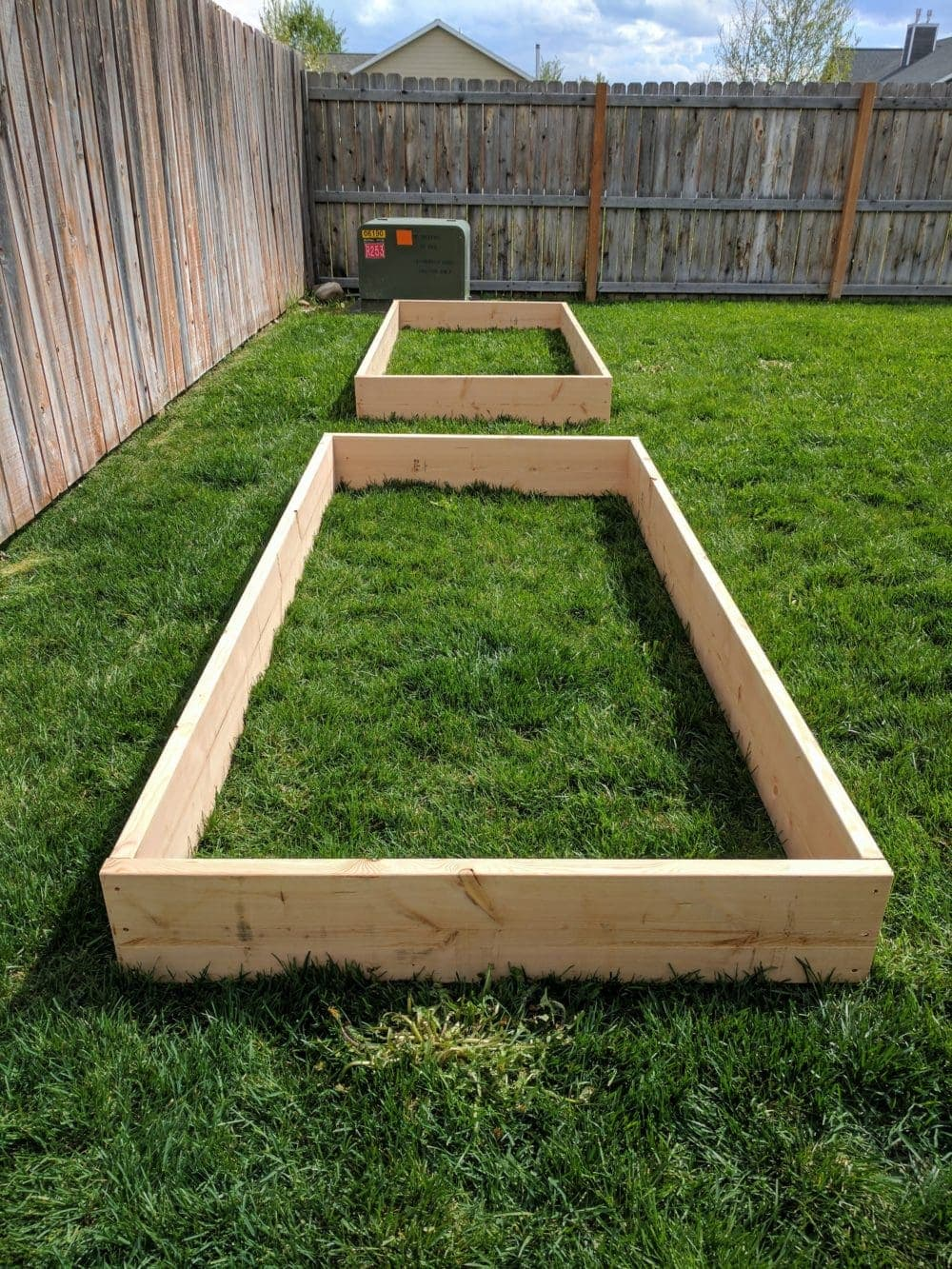 Two empty raised garden bed frames sitting in a grassy fenced yard