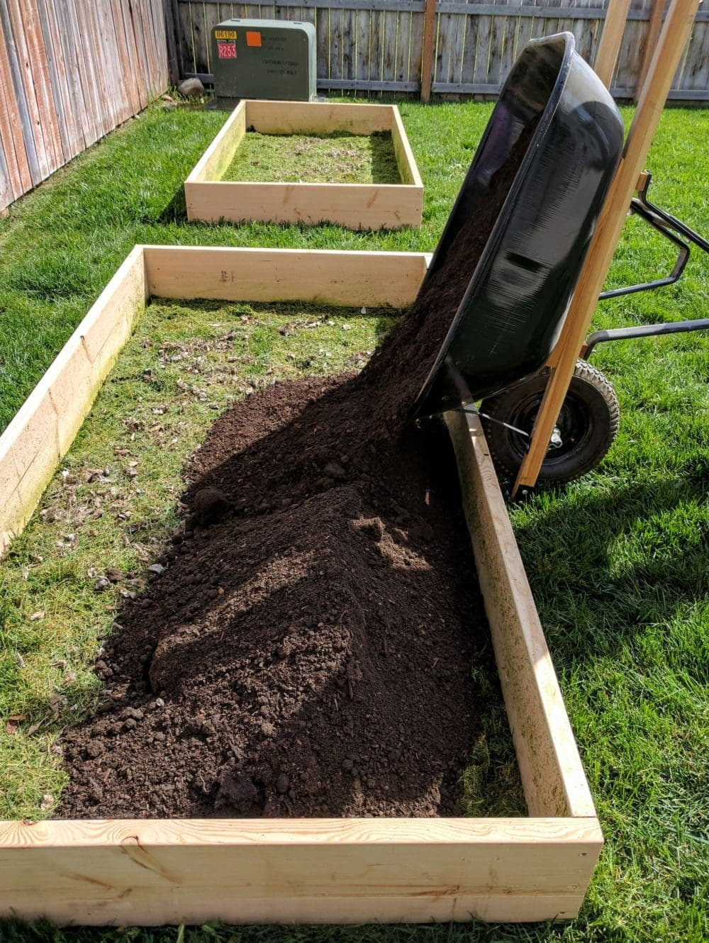 A wheel barrow dumping soil into a raised garden bed