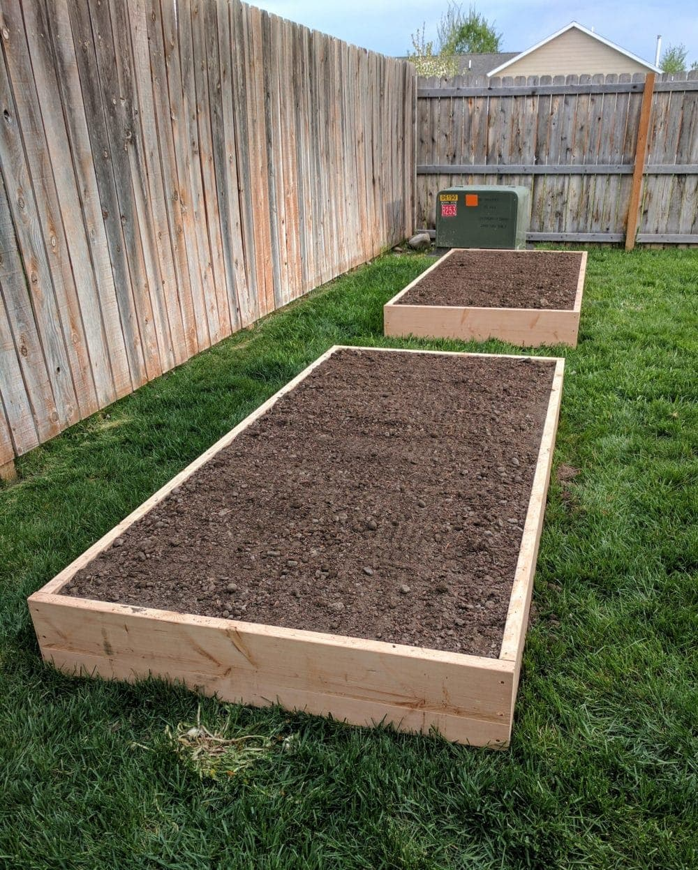 Two raised garden beds full of soil ready to be planted
