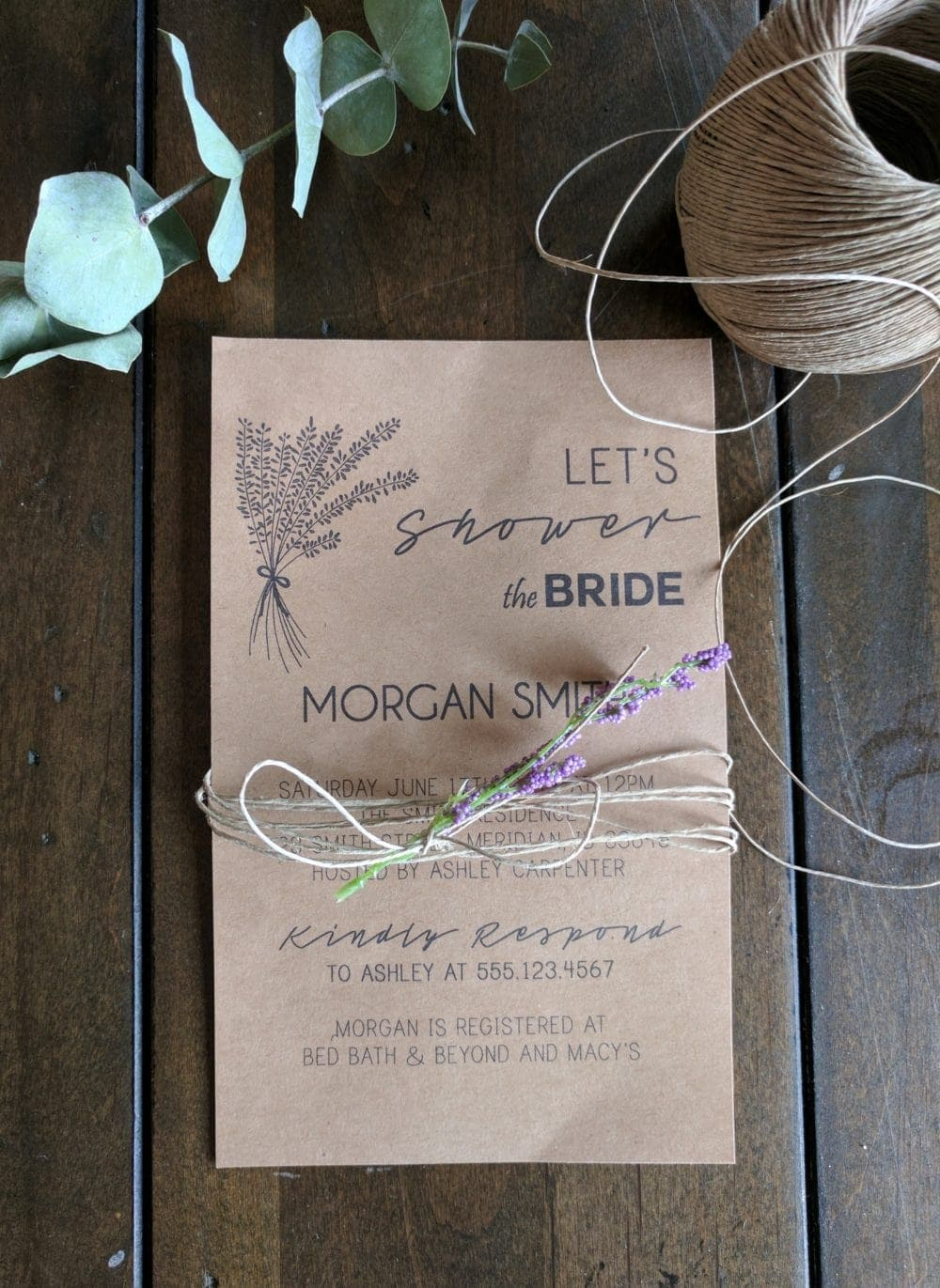 A DIY wedding Invitation sitting on a wood table wrapped in twine with lavender