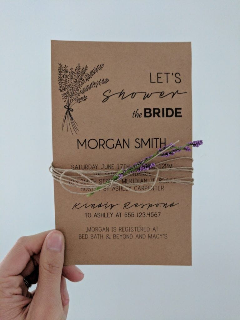 a hand holding up a diy bridal shower invitation wrapped in twine and lavender