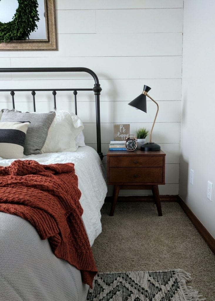 a nightstand styled with books, alarm clock, and a lamp in a farmhouse bedroom
