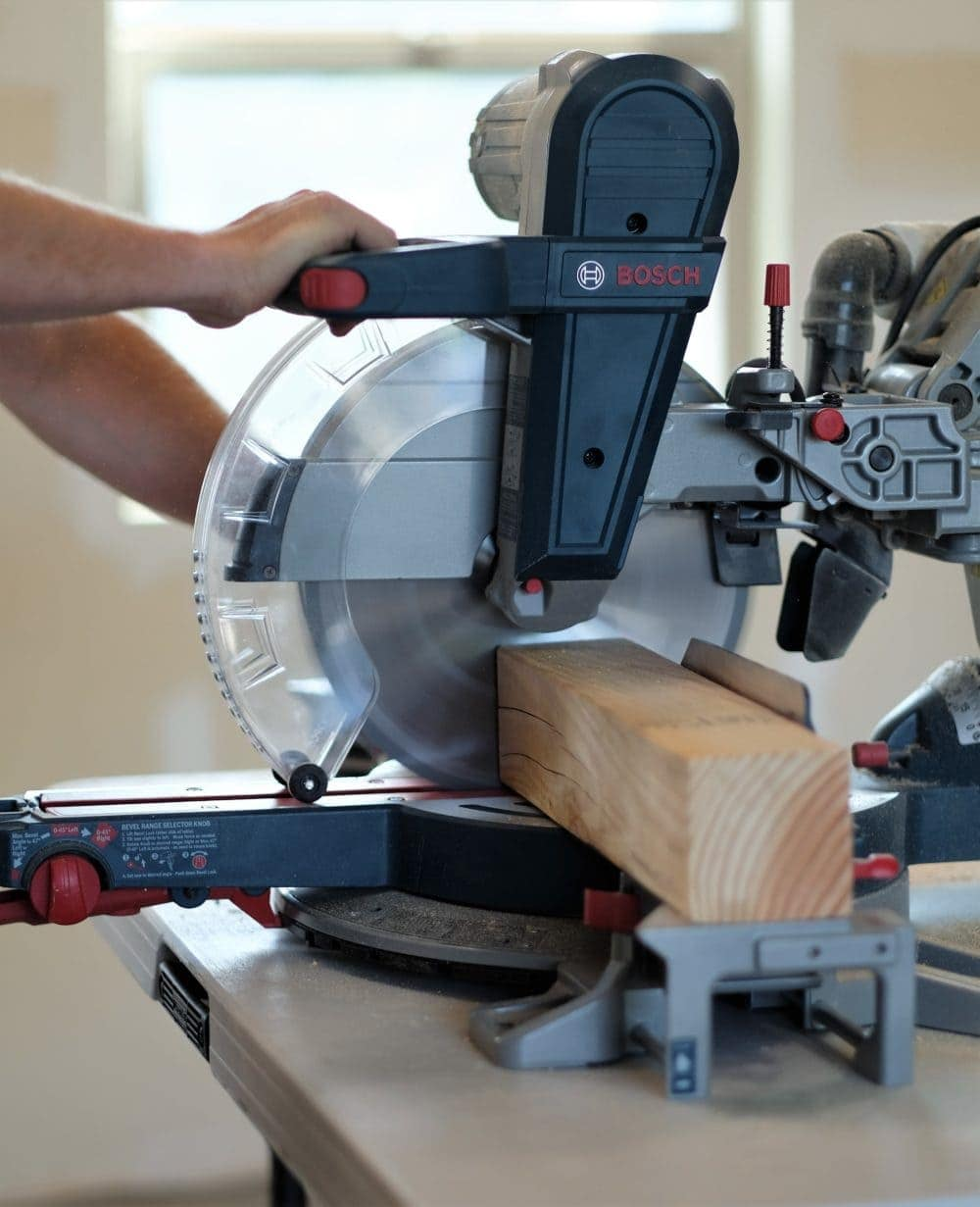 Man using a Bosch Table saw to cut a wood board for a rustic coffee table