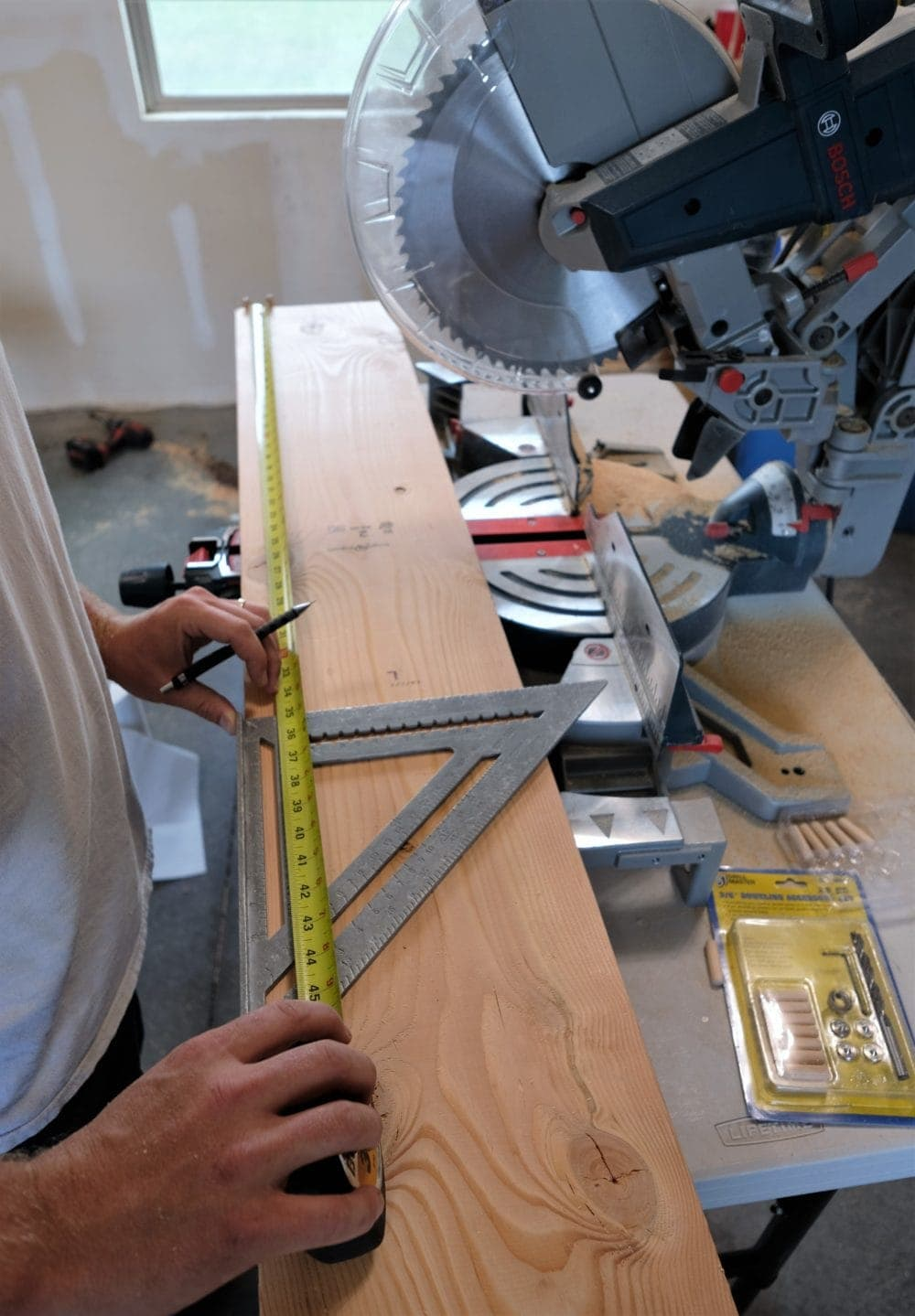 Man measuring a board to make rustic coffee table