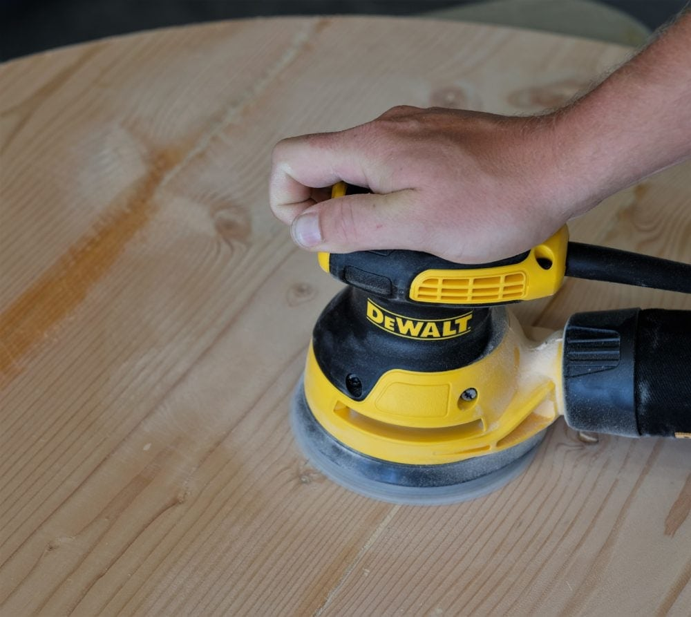Man sanding rustic coffee table with DeWalt sander