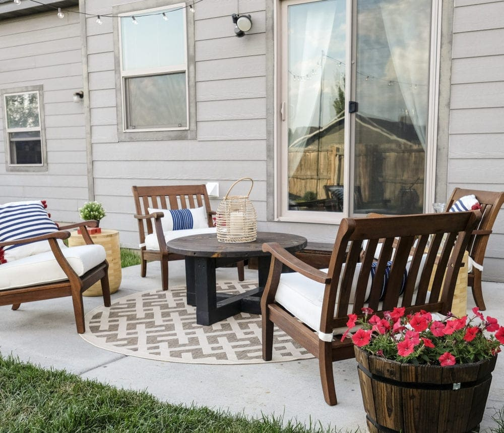 patio makeover with four chairs around a rustic coffee table