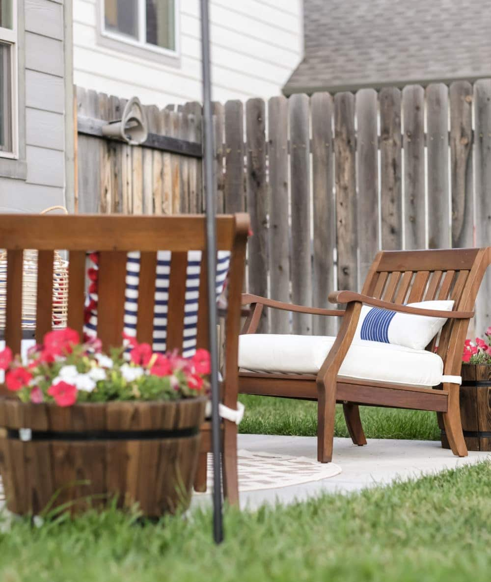 outdoor patio with flowers in barrels and wood lawn chairs
