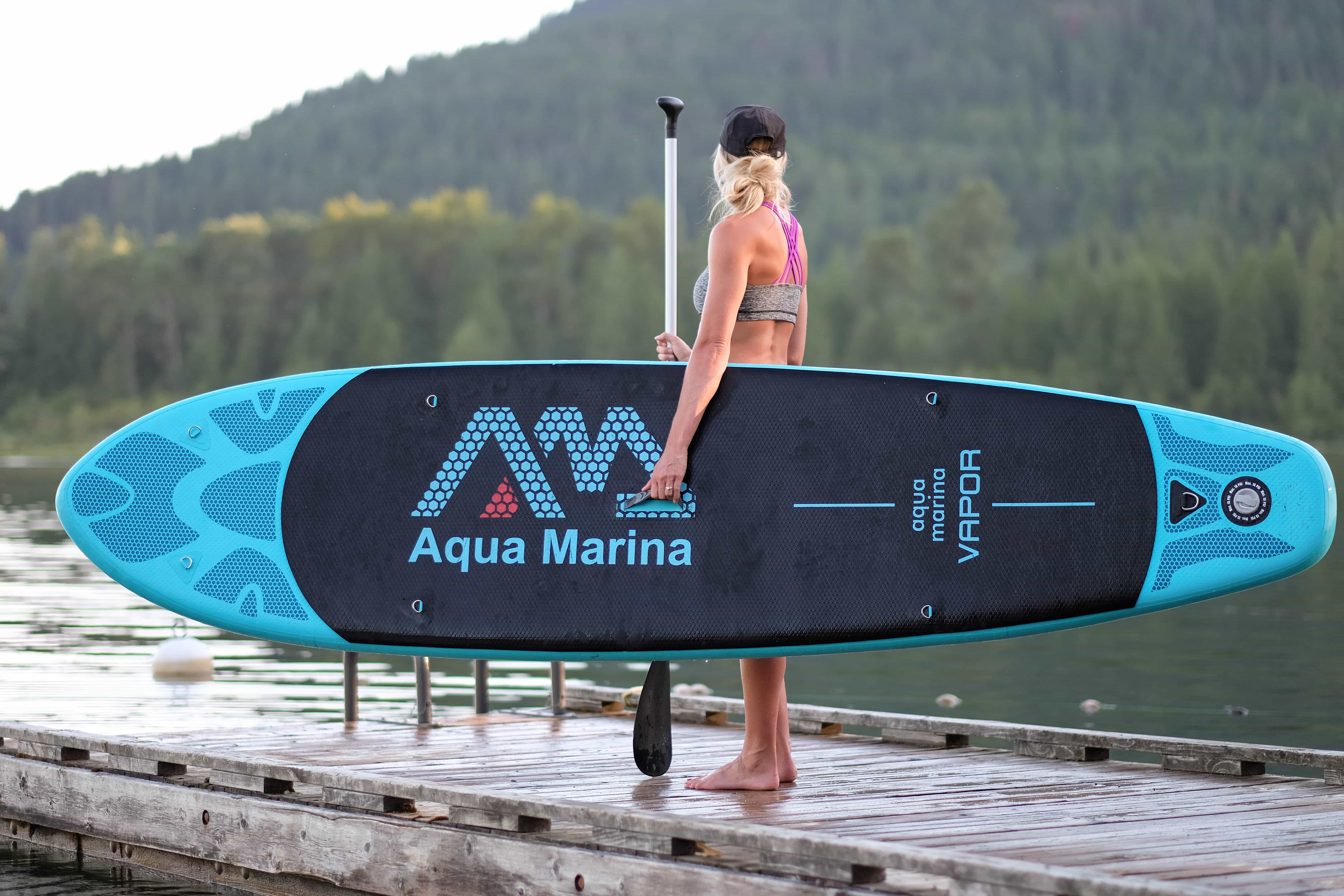 girl holding inflatable SUP standing on a dock looking over the lake