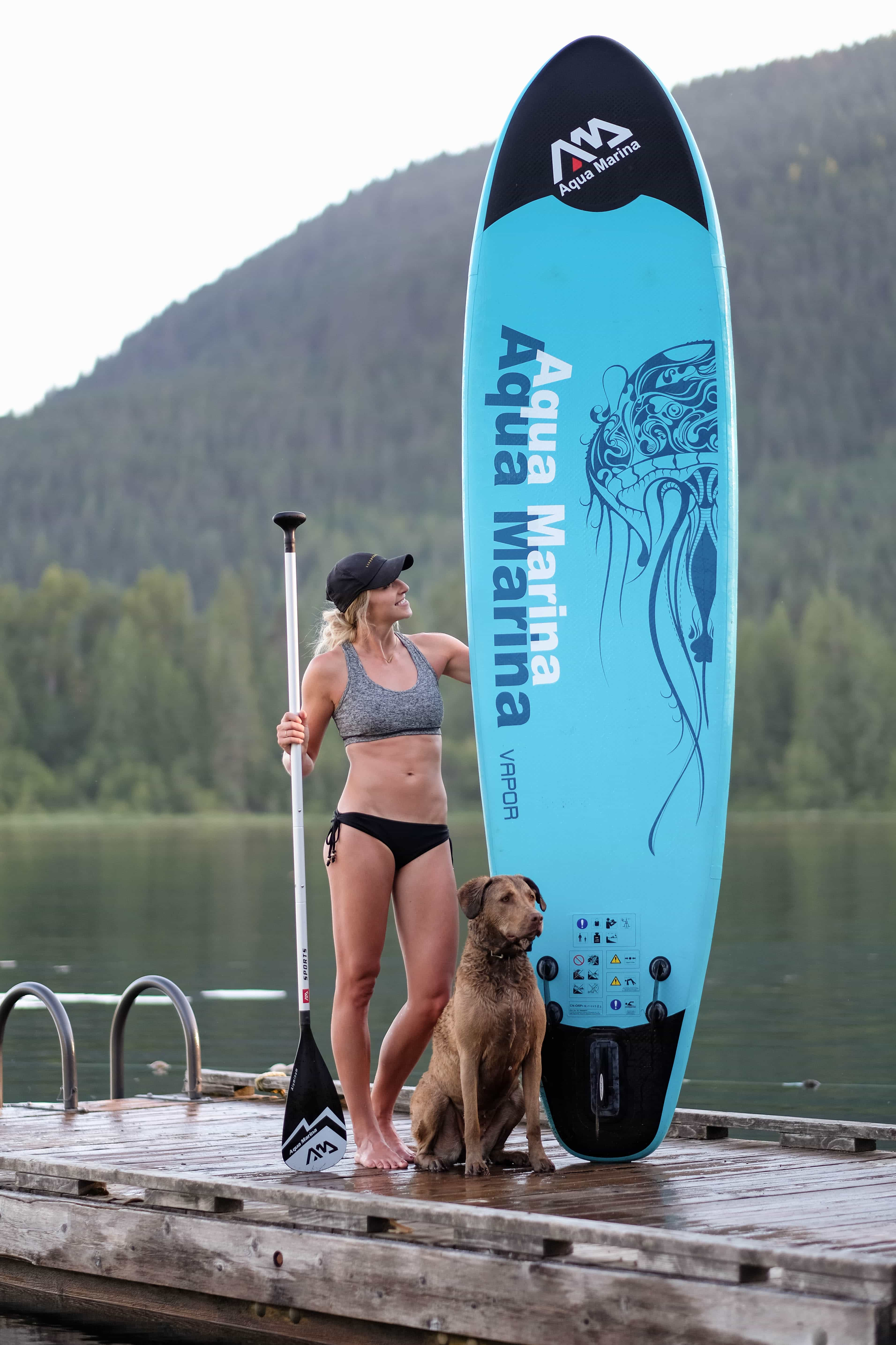 girl holding her inflatable sup on a dock with a dog