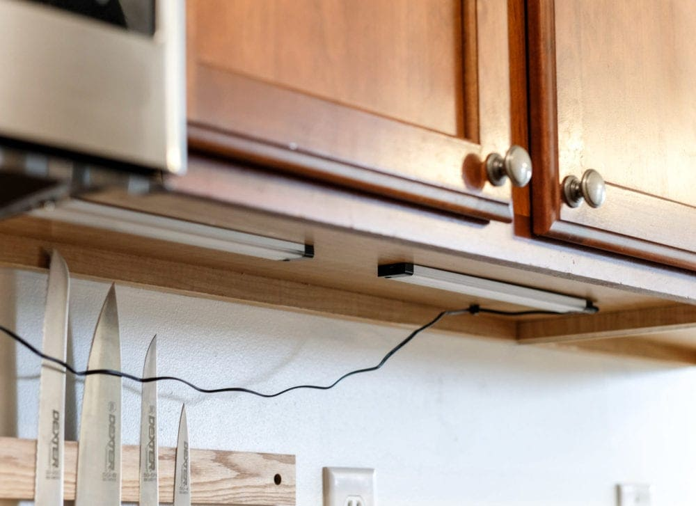 fastening an under cabinet light to the bottom of a kitchen cabinet