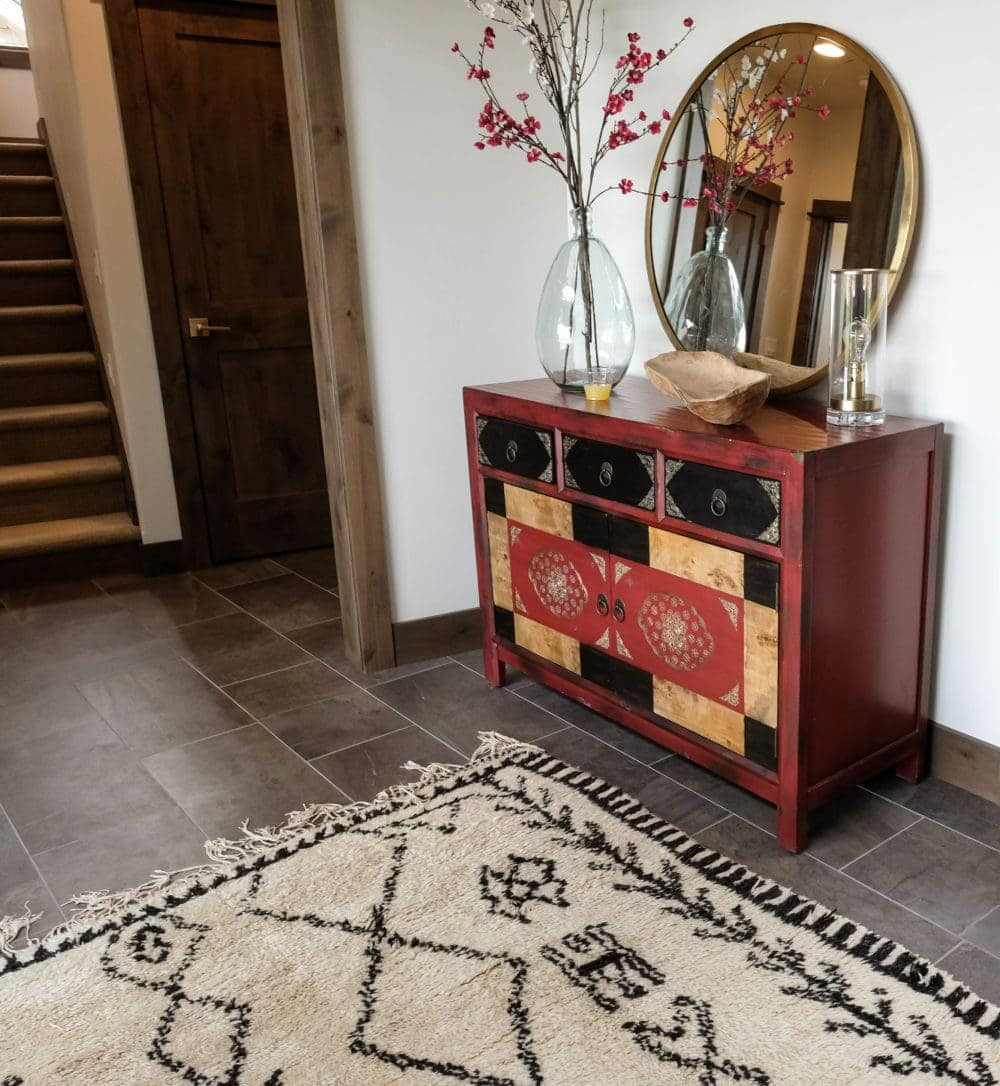 Parade of Homes entryway with grey floor, tan rug, and red dresser