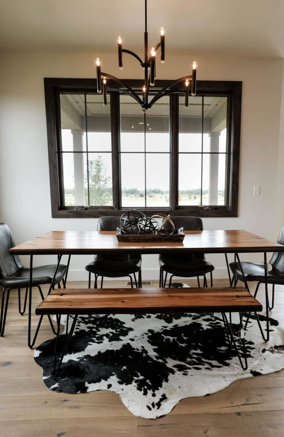 Parade of Homes dining room with wood table, and cowhide rug underneath