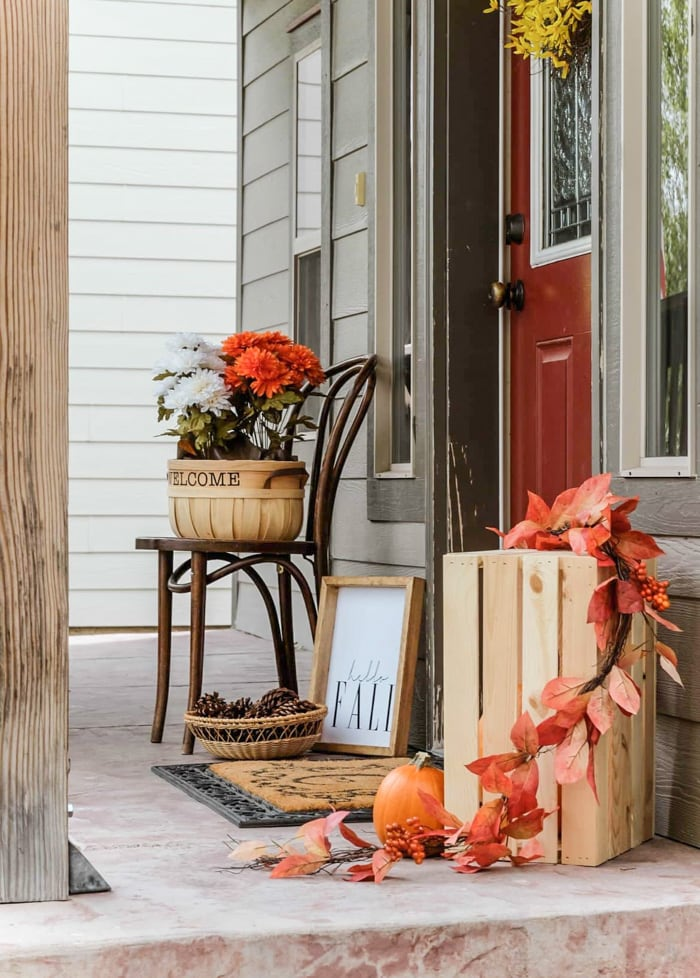 Fall front porch decor with orange and white flowers, pinecones in a basket and pumpkins in a crate