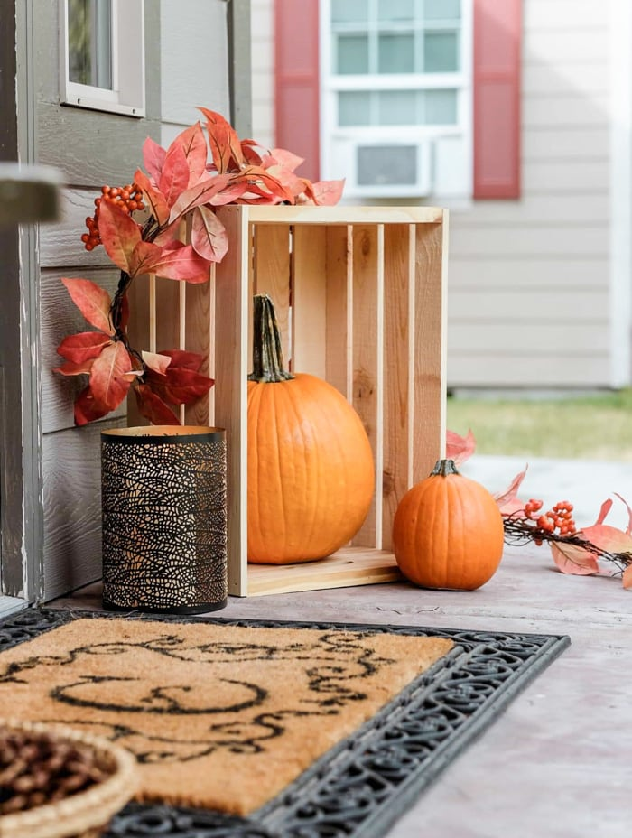 Fall front porch decor including a welcome mat, candle, pumpkins in a crate and a leaf garland