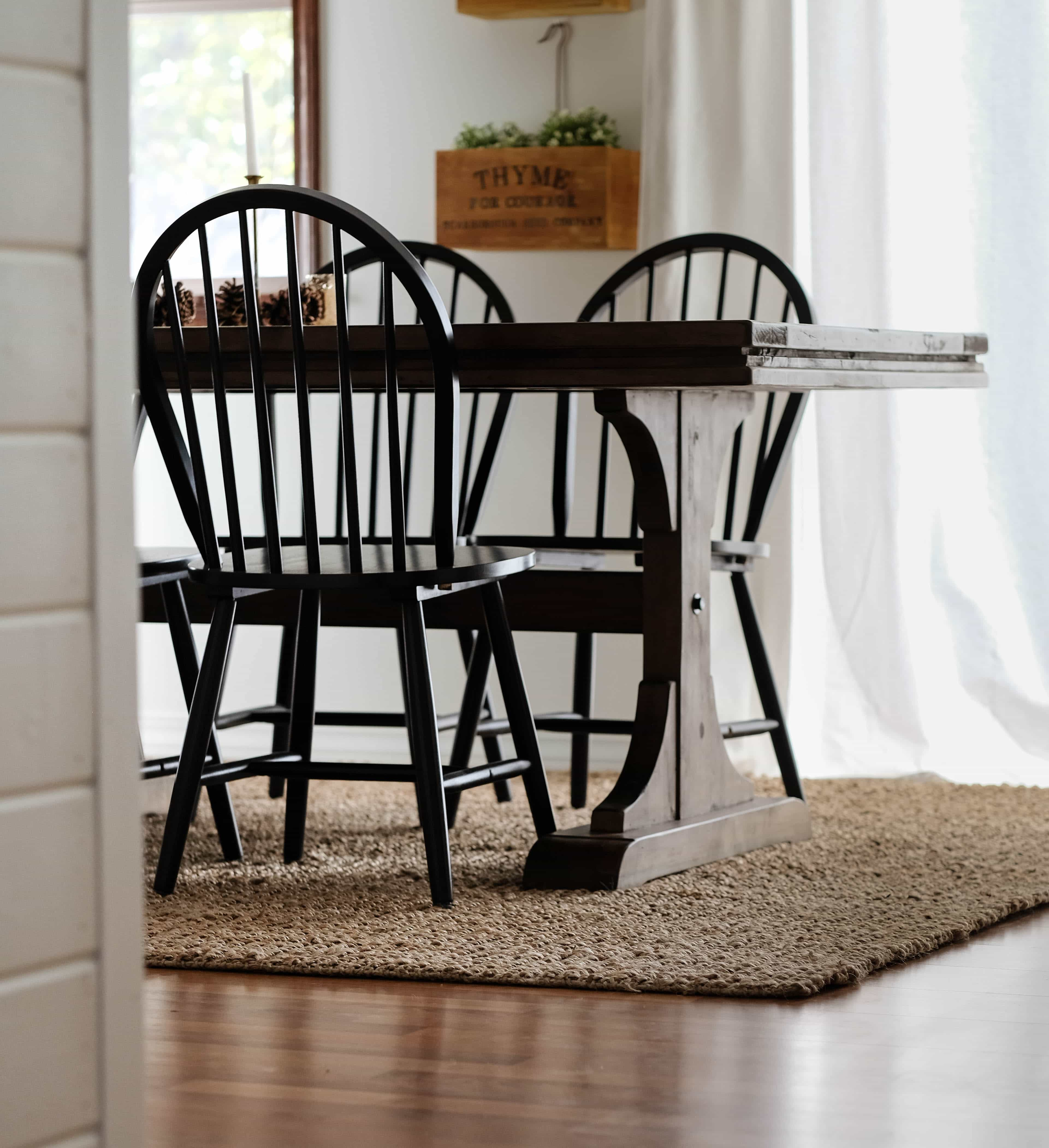 dining room with table and chairs on top of a jute rug
