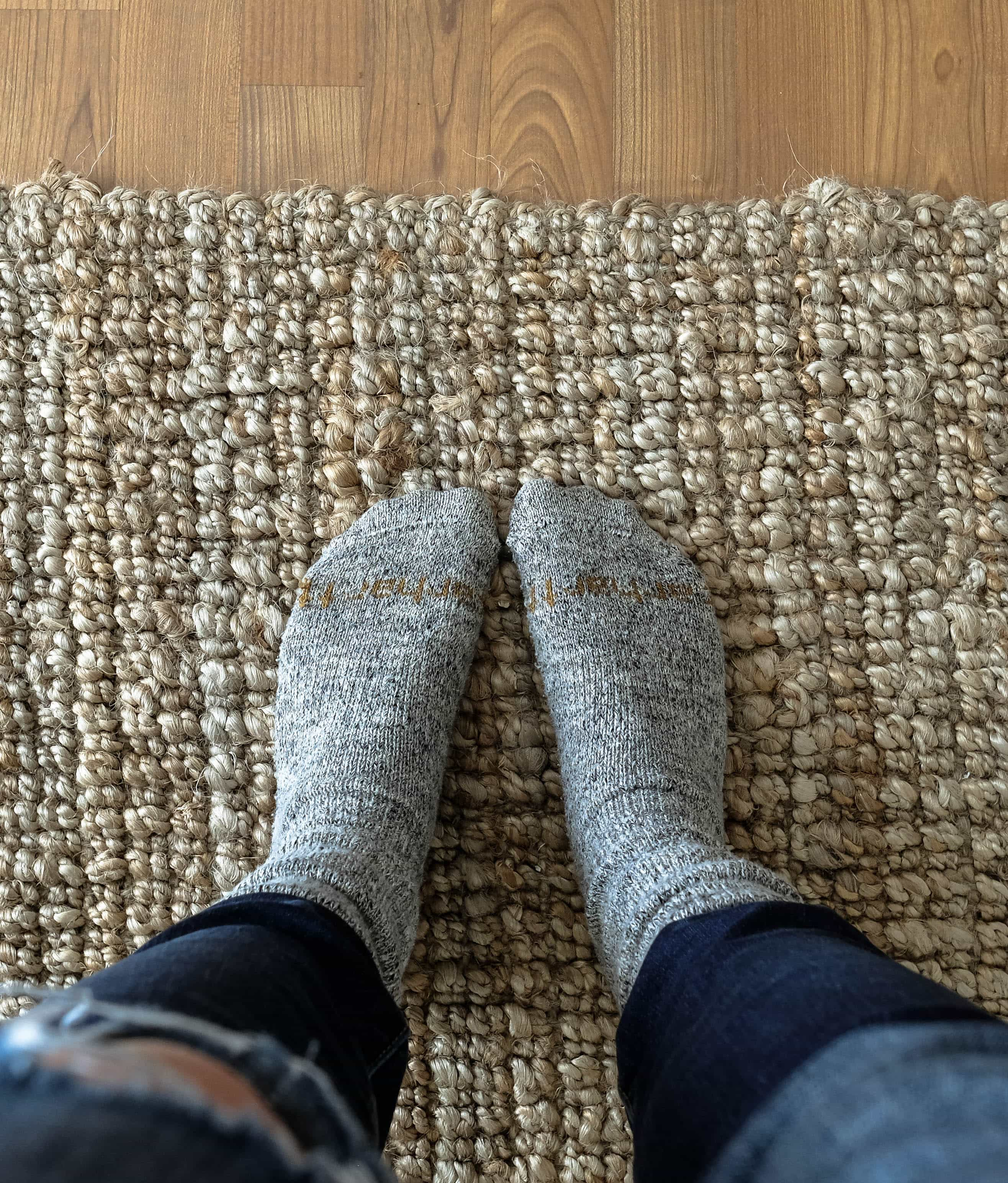 Close up of feet wearing wool socks standing on a jute rug