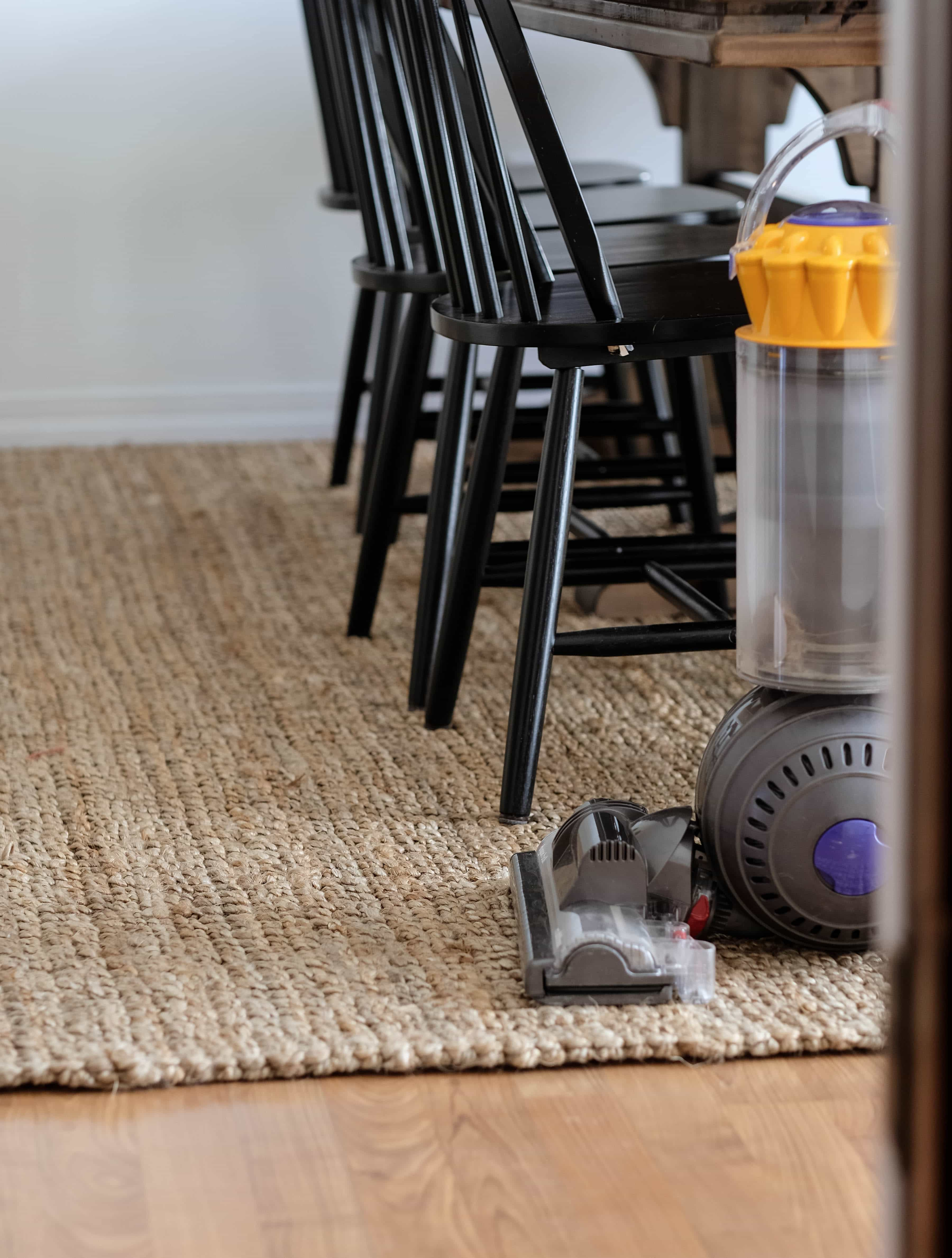 Jute rug in dining room with table and chairs. Dyson vacuum in foreground.