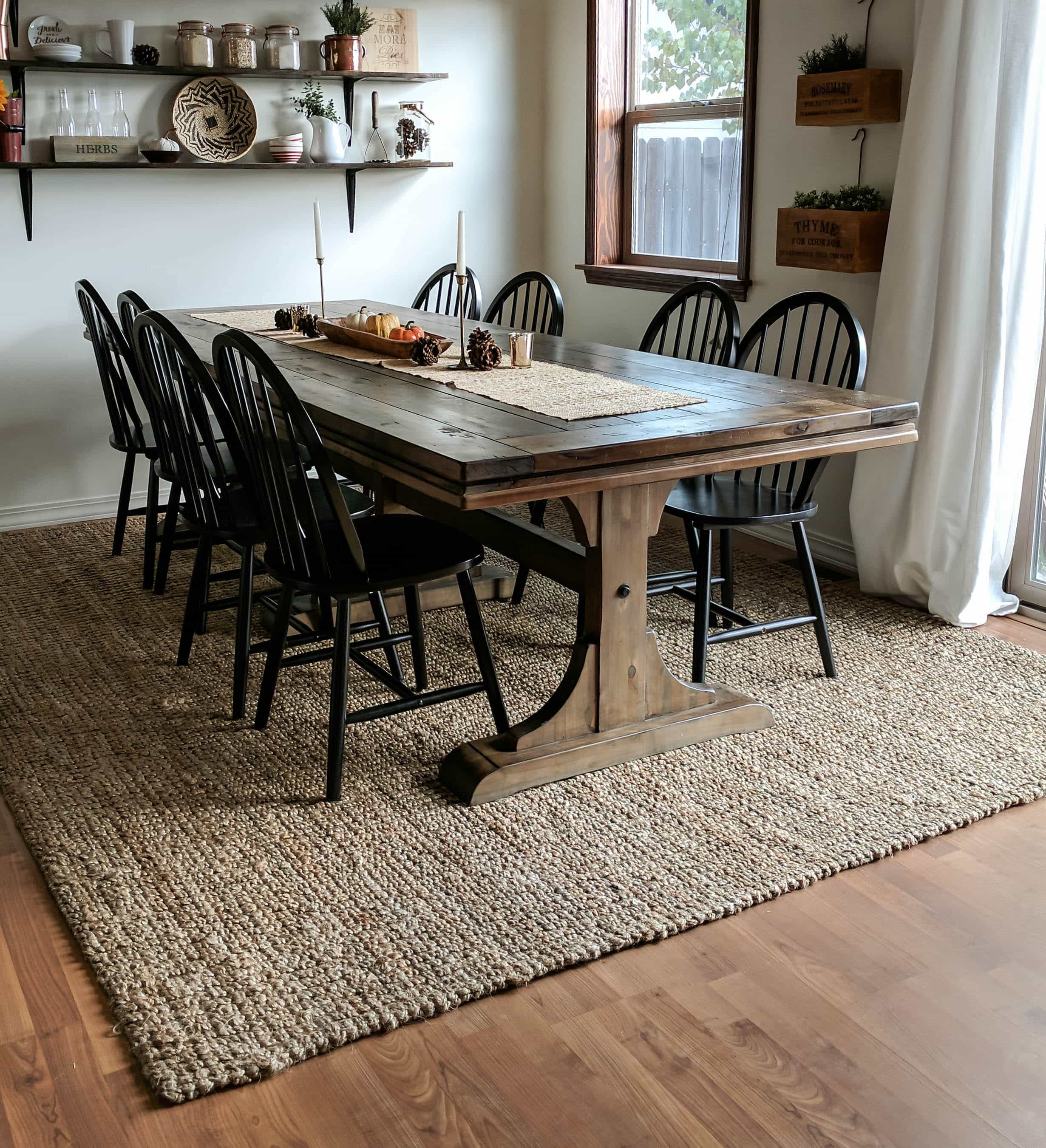 full room picture of dining room with jute rug underneath long wood table and 8 black wood chairs