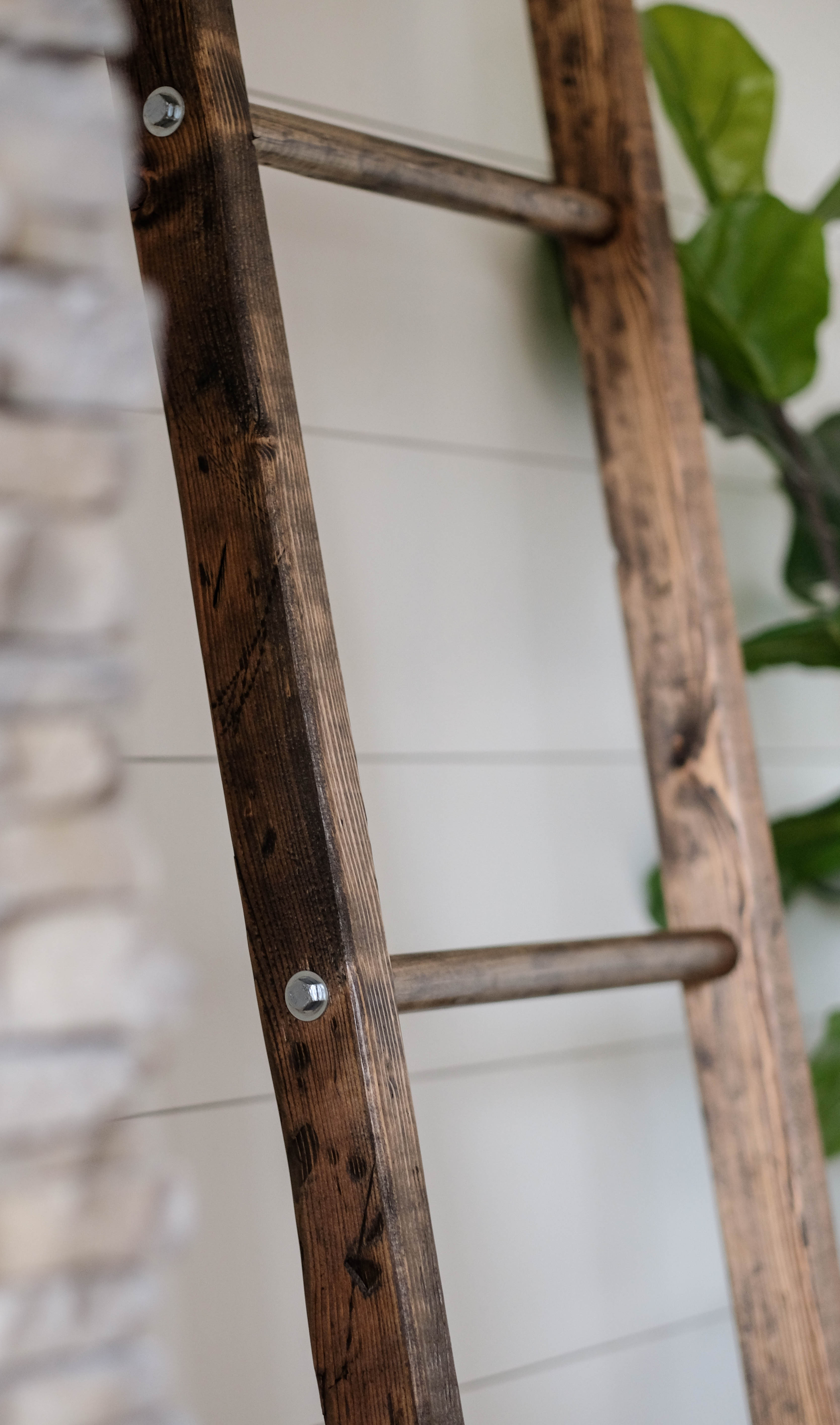 A walnut stained blanket ladder leaning against a white shiplap wall