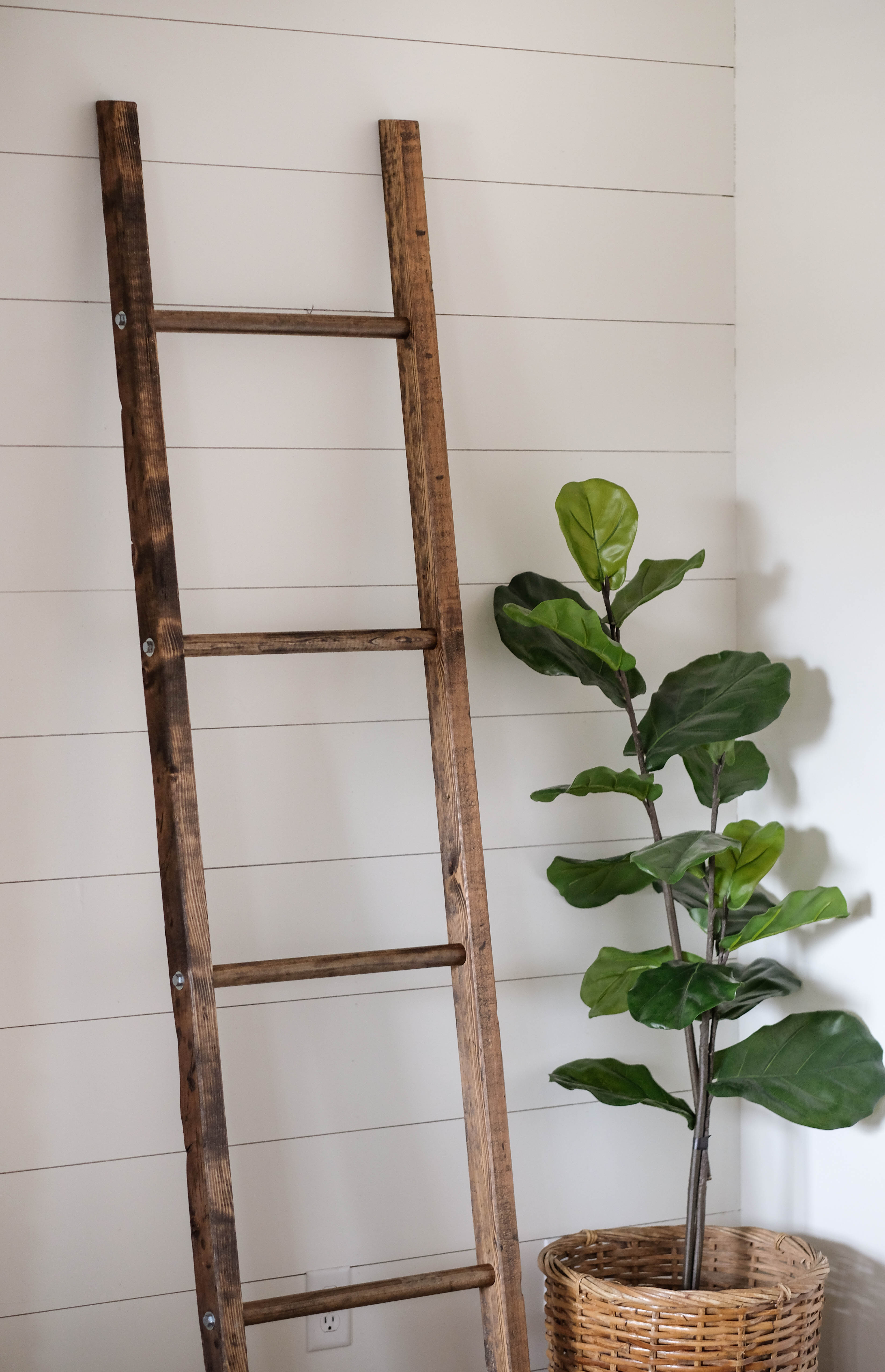 A walnut stained blanket ladder leaning against a white shiplap wall.