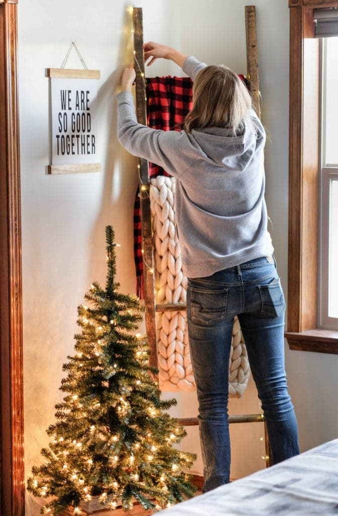 A woman styling a blanket ladder for the holidays