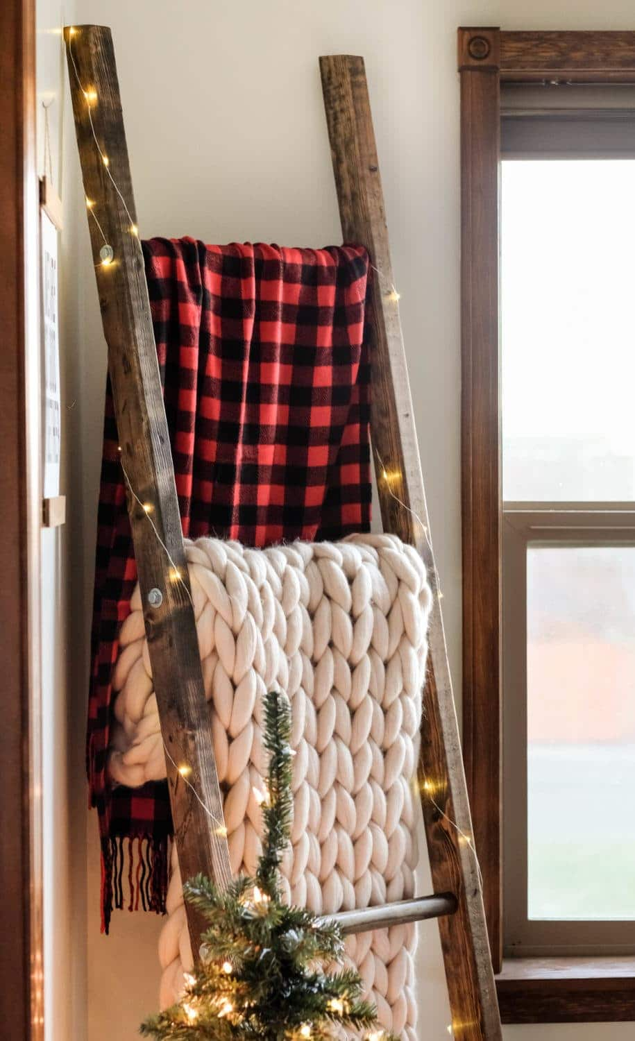 a blanket ladder holding blankets with christmas lights strung on it