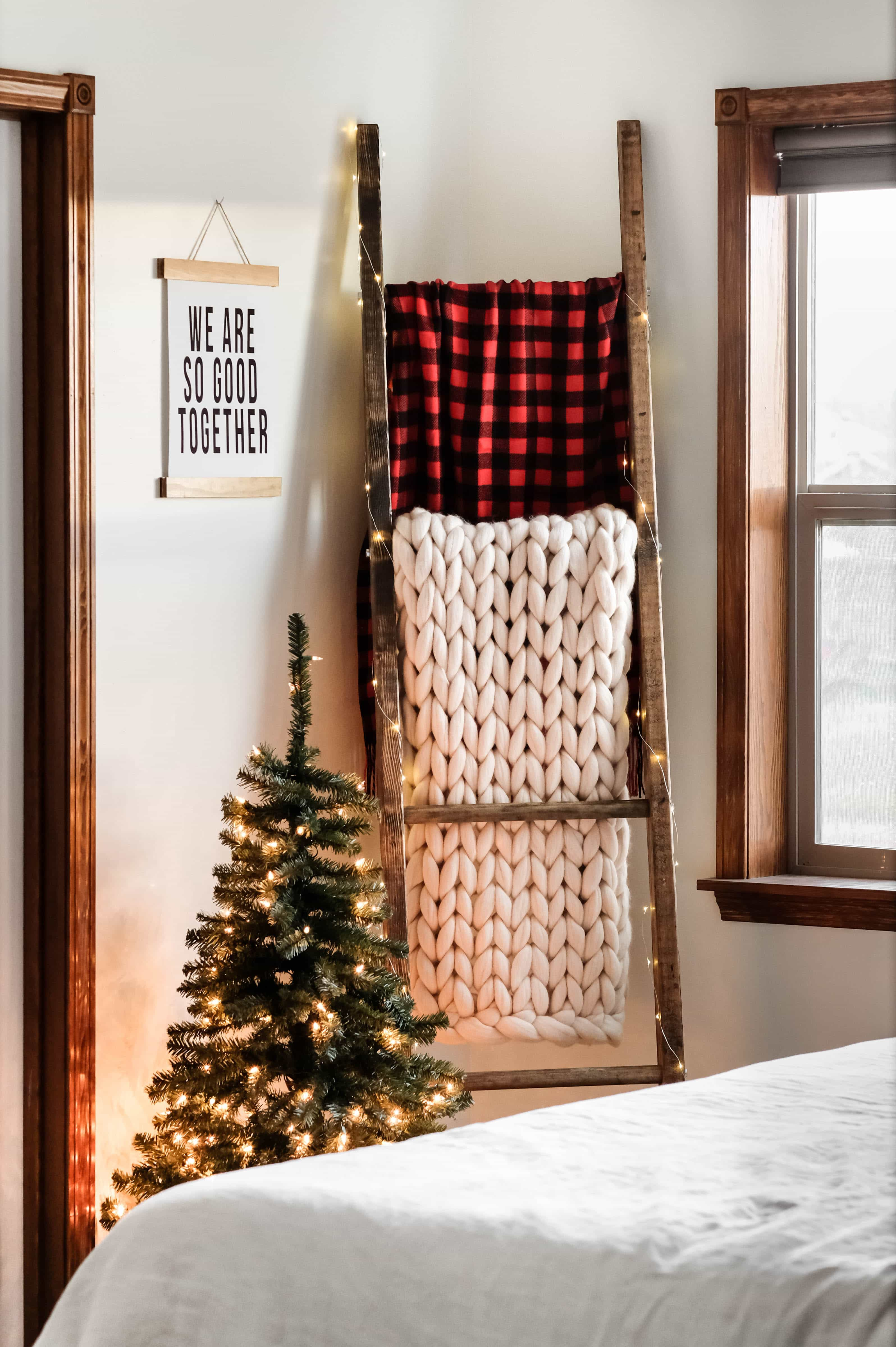 A blanket ladder with holding a white woven blanket, and a red buffalo check blanket
