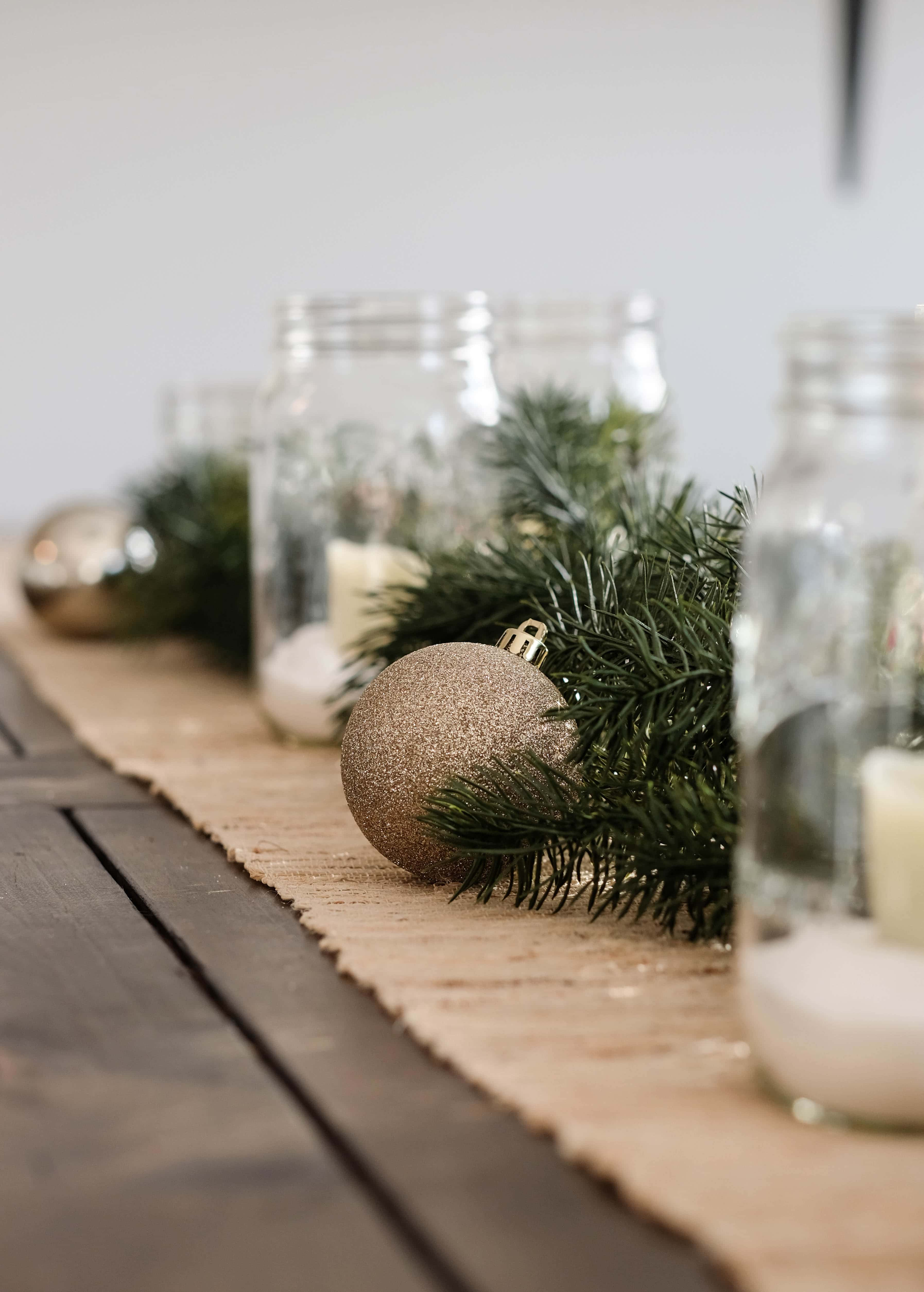 christmas dining table centerpiece with mason jar candle holders and ornaments