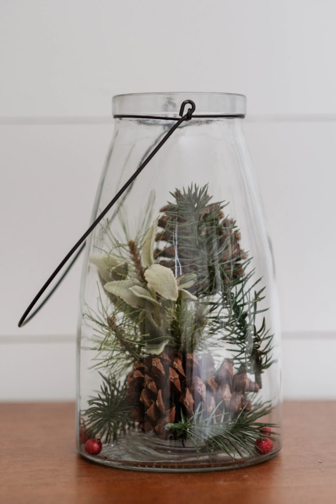 Christmas decor using a glass lantern filled with pinecones and pine tree clippings