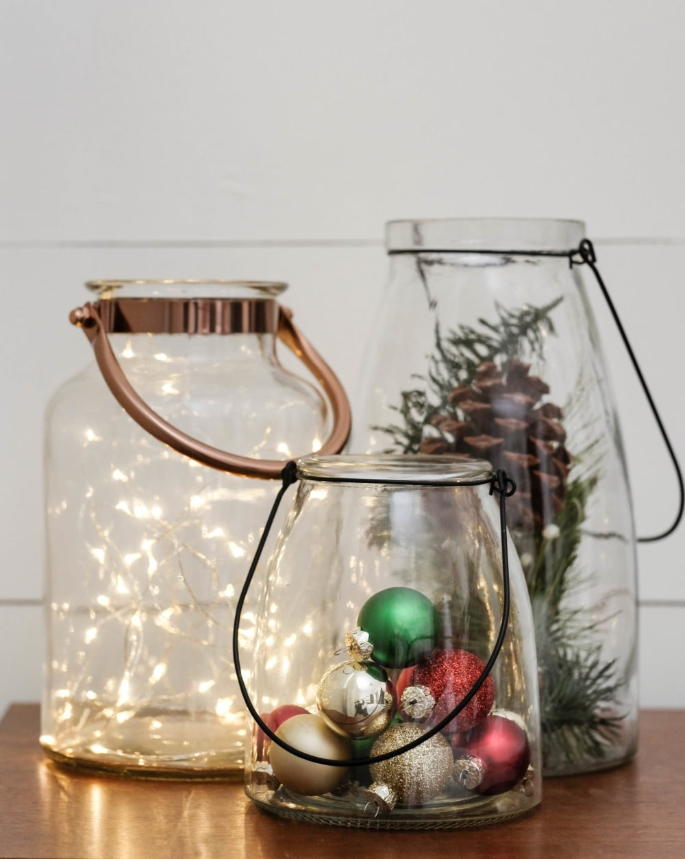Christmas decor using 3 glass lanterns filled with twinkle lights, Christmas ornaments and pinecones