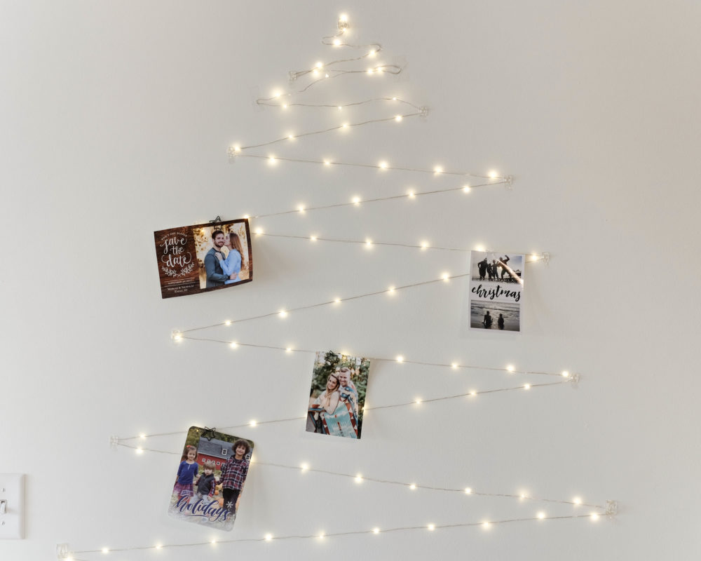 Christmas decor ideas using twinkle lights in the shape of a tree with holiday cards