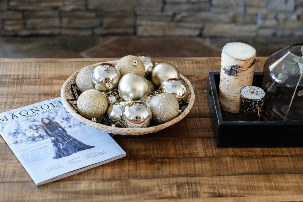 christmas decor idea on the coffee table with bowl full of ornaments and magnolia journal