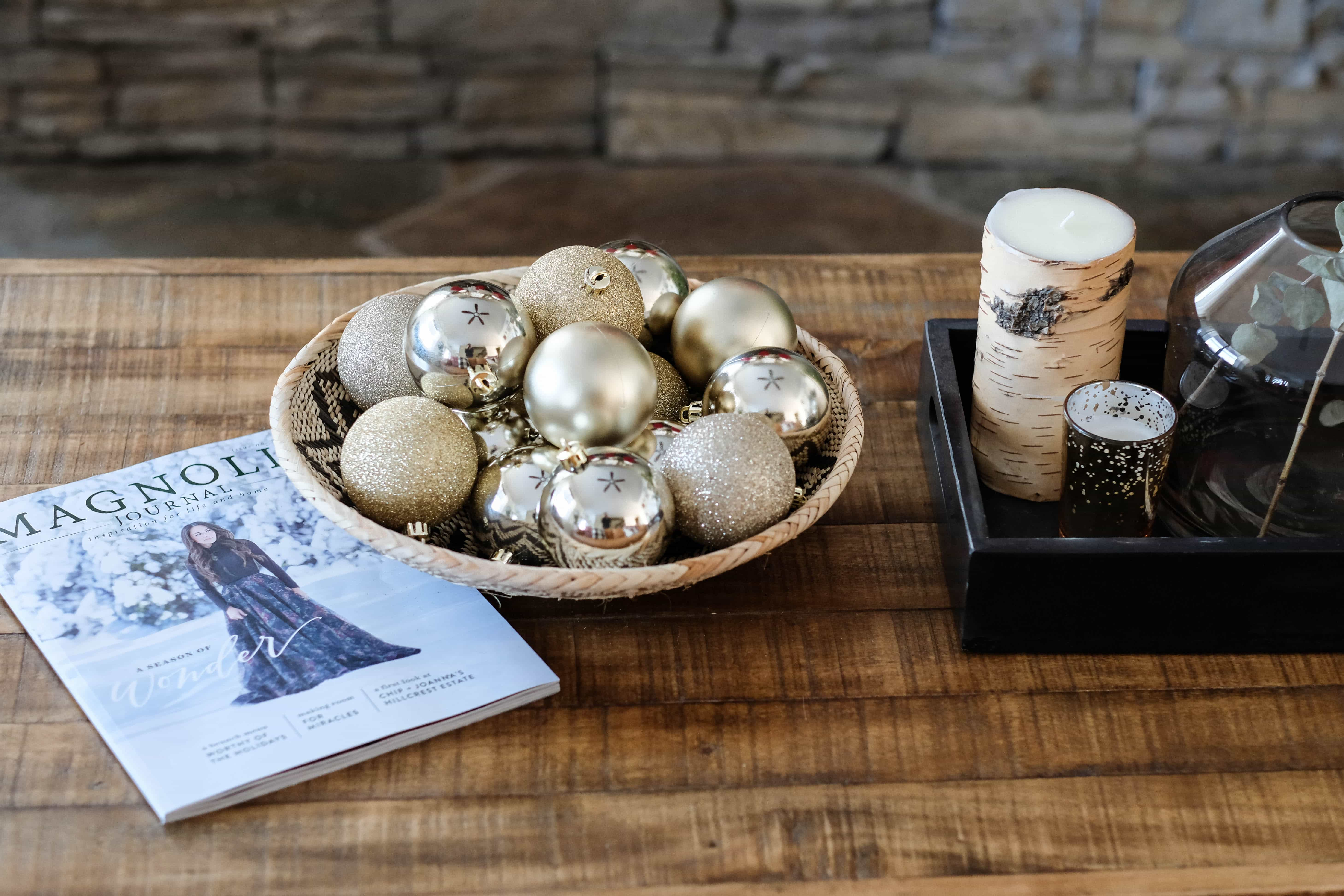 christmas coffee table with bowl full of ornaments and magnolia journal