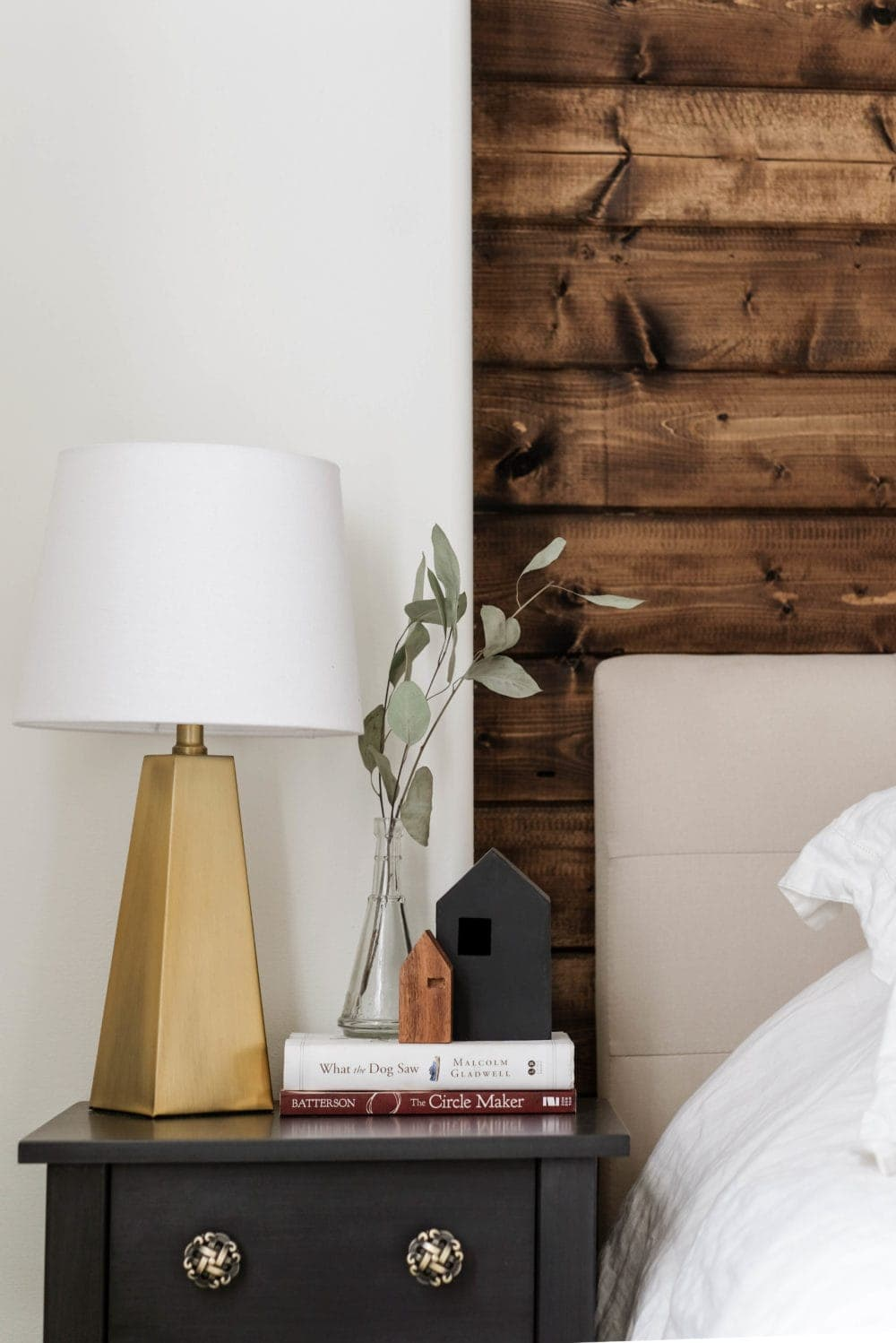 Christmas bedroom decor ideas including a nightstand styled with a gold lamp, books and a plant