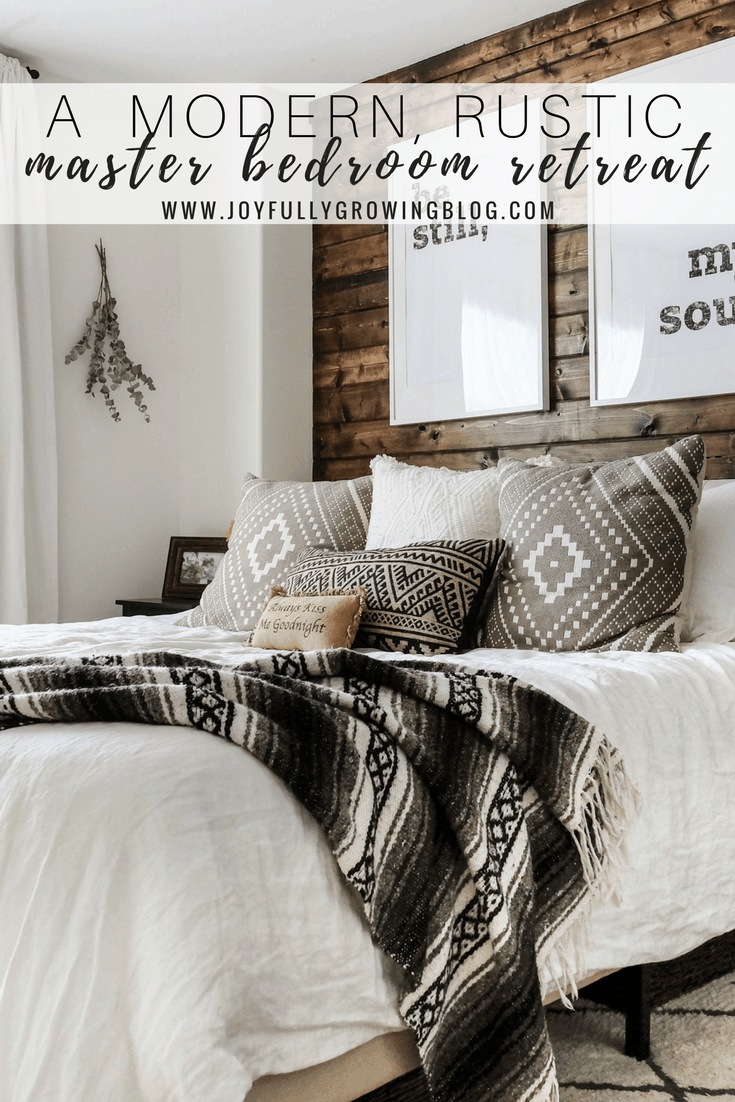 "A rustic bedroom with a closeup of the bedding including throw pillows and blanket, up against a wood plank wall. Text overlay ""A Modern, Rustic Master Bedroom Retreat - www.joyfullygrowingblog.com"""