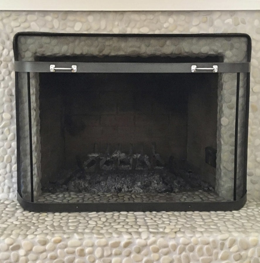 empty fireplace with metal screen cover