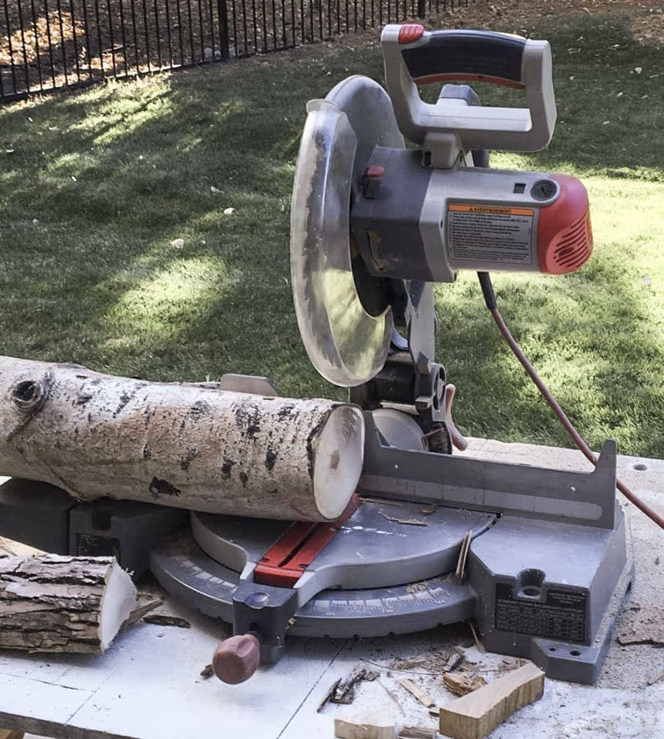 A miter saw sitting on a table outside cutting logs into small round pieces