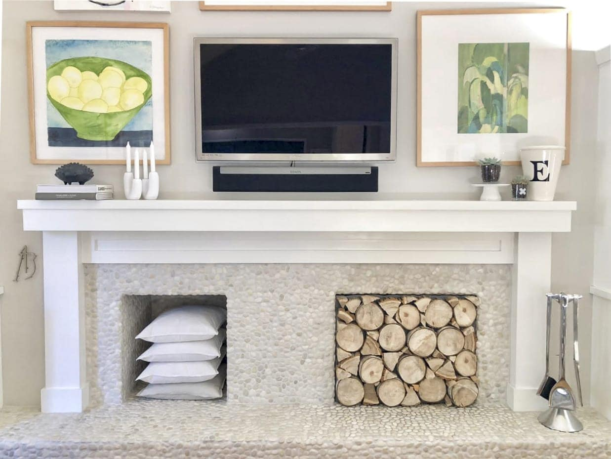 Fireplace mantle with art and TV hung above it and stacked logs in the fireplace insert
