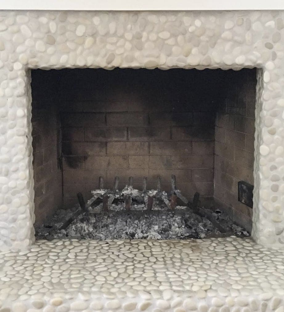 Empty fireplace opening with ashes inside and small pebble rocks surrounding it